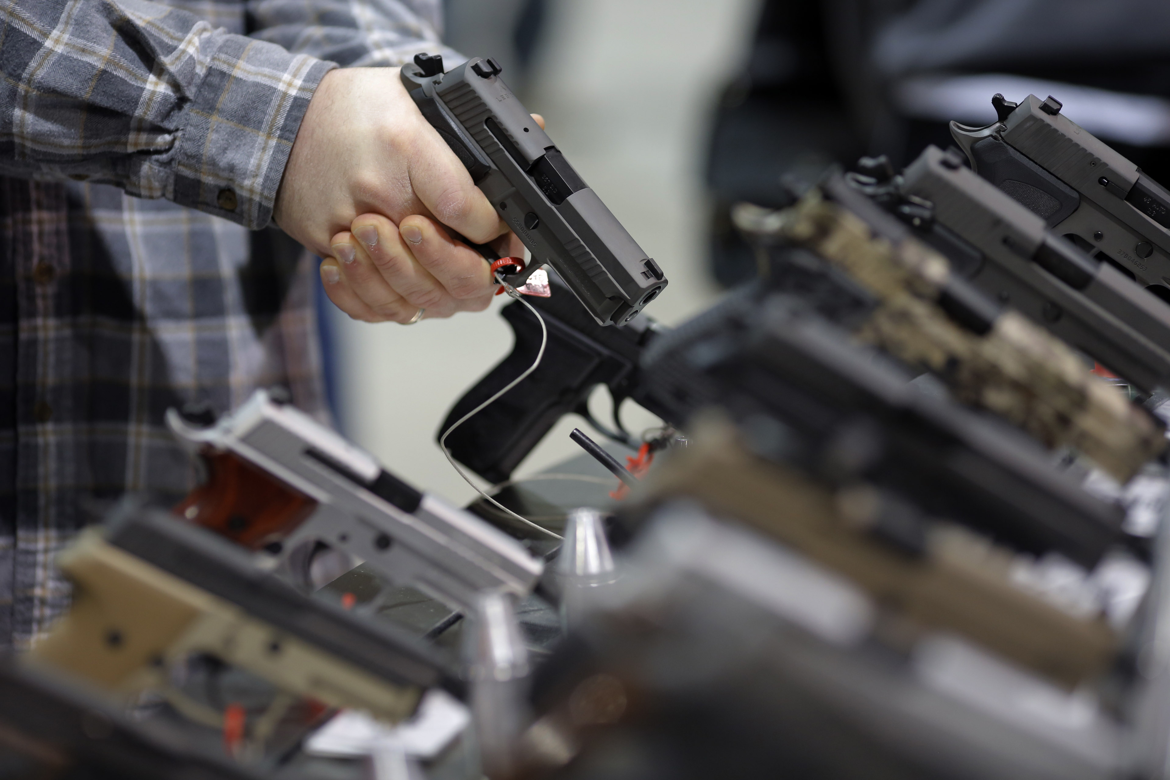A visitor holds a pistol at a gun display during a National Rifle Association outdoor sports trade show on February 10, 2017 in Harrisburg, Pennsylvania.