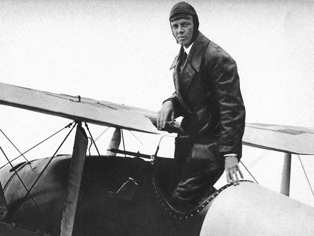 Charles Lindbergh (1902-74) in his flying kit standing in the Spirit of St Louis, the plane in which he made the first non-stop Atlantic air crossing in 1927.