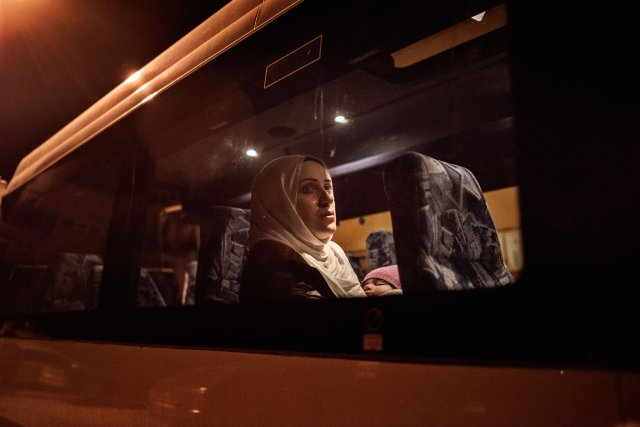 Syrian refugee Taimaa Abazlii weeps as she sits on the bus in front of her new apartment after a long, grueling day of travel and unheaval once again from Athens to their new home in Polva, Estonia, April 20, 2017.  The family, along with Muhannad's brother's family of Mufeed and Iyman Ateek and their two children, were relocated to a small village of 6000 people in the middle of the forest, called Polva; they feared it would be impossible to integrate and make a life in such a remote place.  After over one year of traveling from war-town Syria, making their way from Turkey to Greece, waiting in greece for asylum, the family is finally relocating to Estonia.