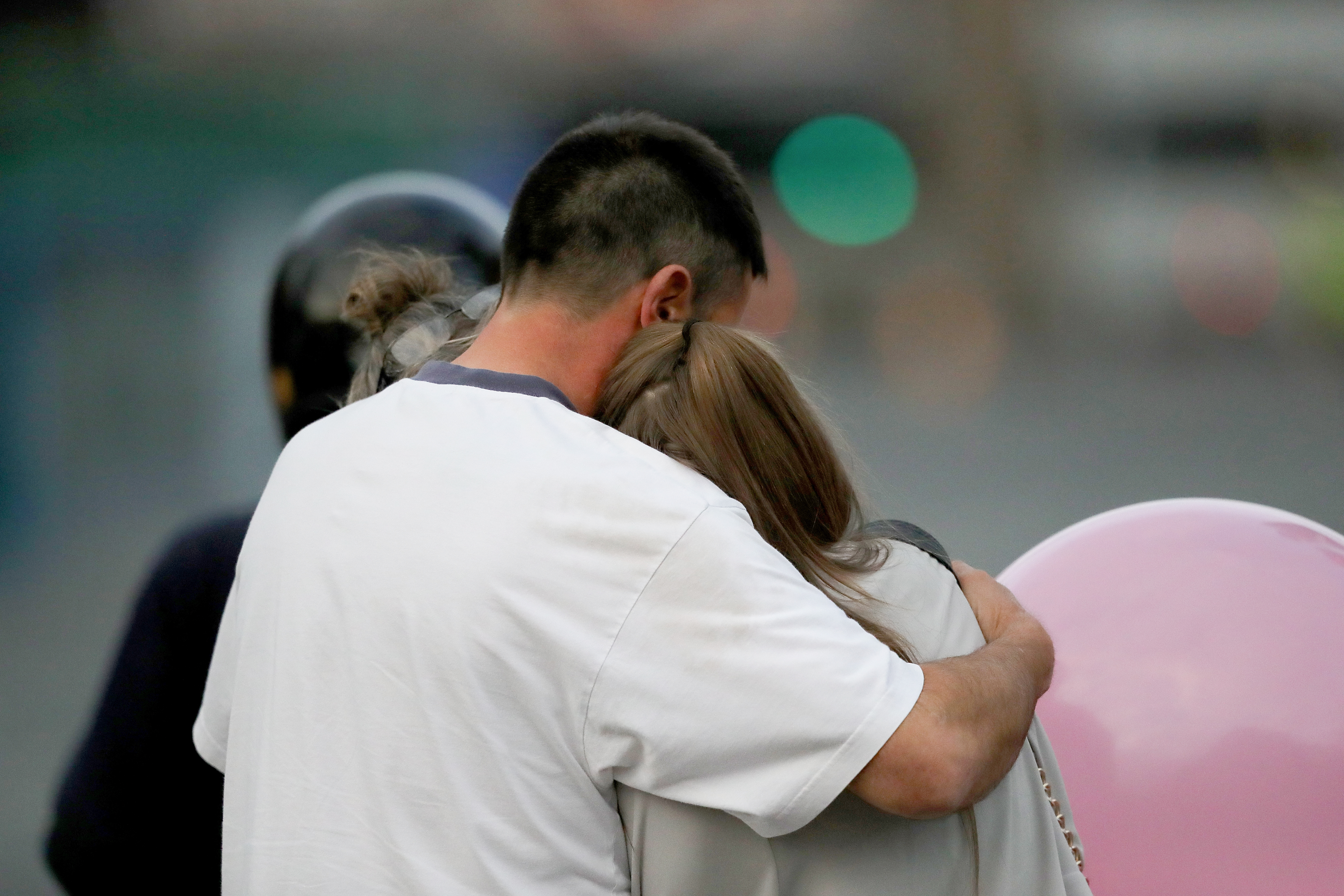A man embraces a woman and a teenager as he collects them from the Park Inn Hotel where they were given refuge after last nights explosion at the Manchester Arena on May 23, 2017 in Manchester, England.