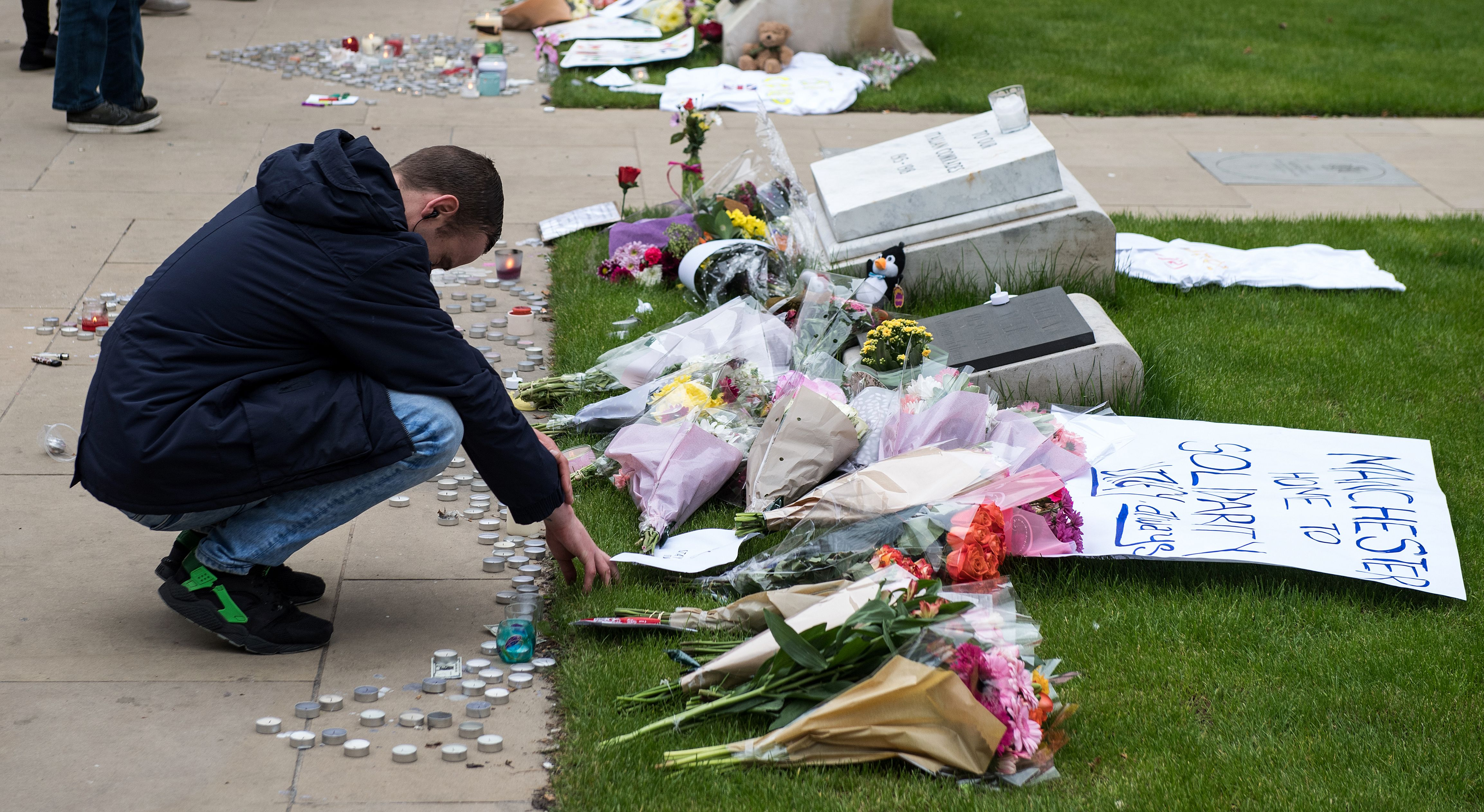 A man reacts as he view floral tributes, messages and candles in Albert Square in Manchester, northwest England on May 24, 2017.