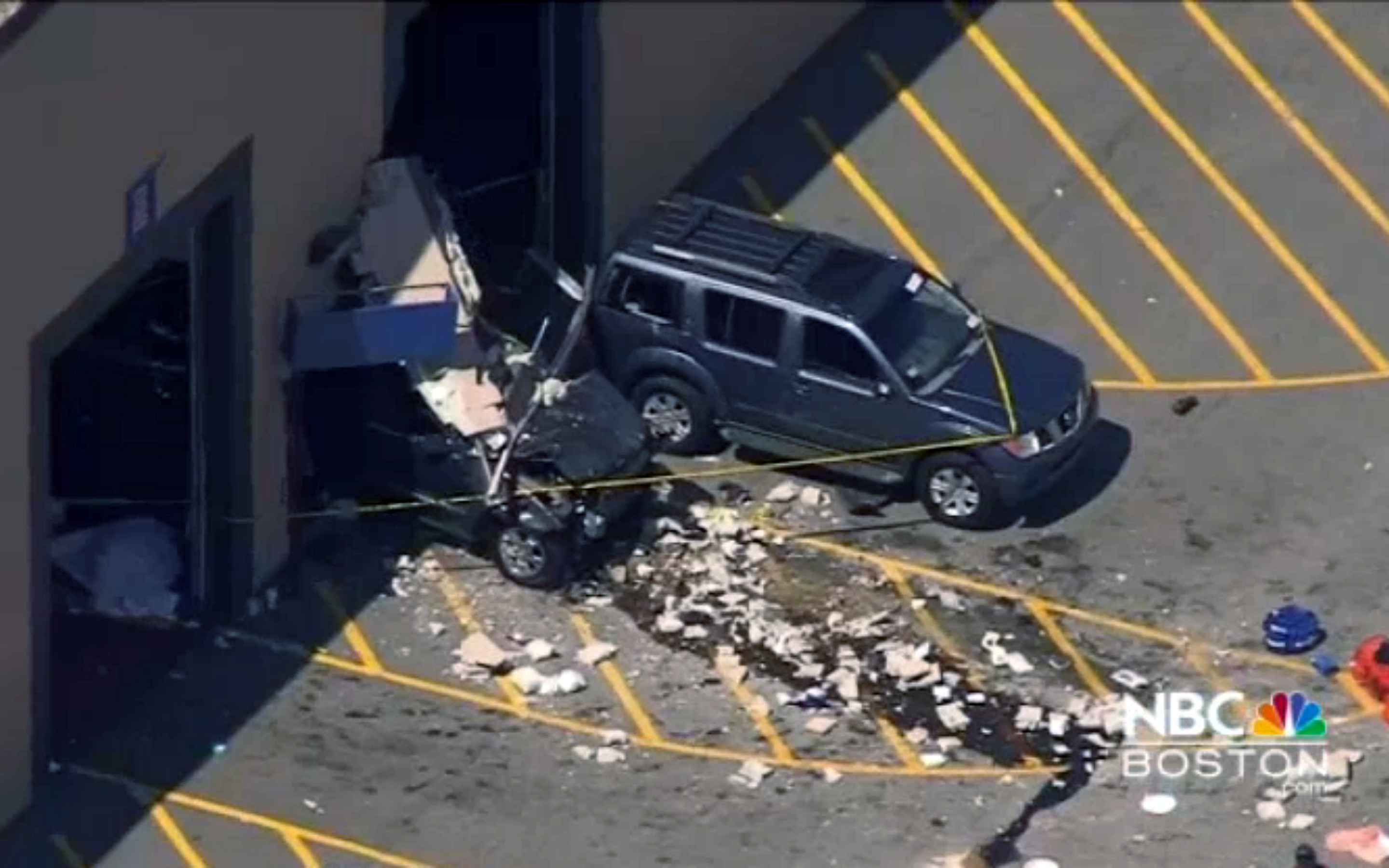 This still image from video provided by NBC Boston shows wreckage after a vehicle suddenly accelerated at an auto auction and struck several people before it crashed through a wall of the building on May 3, 2017, in Billerica, Mass.