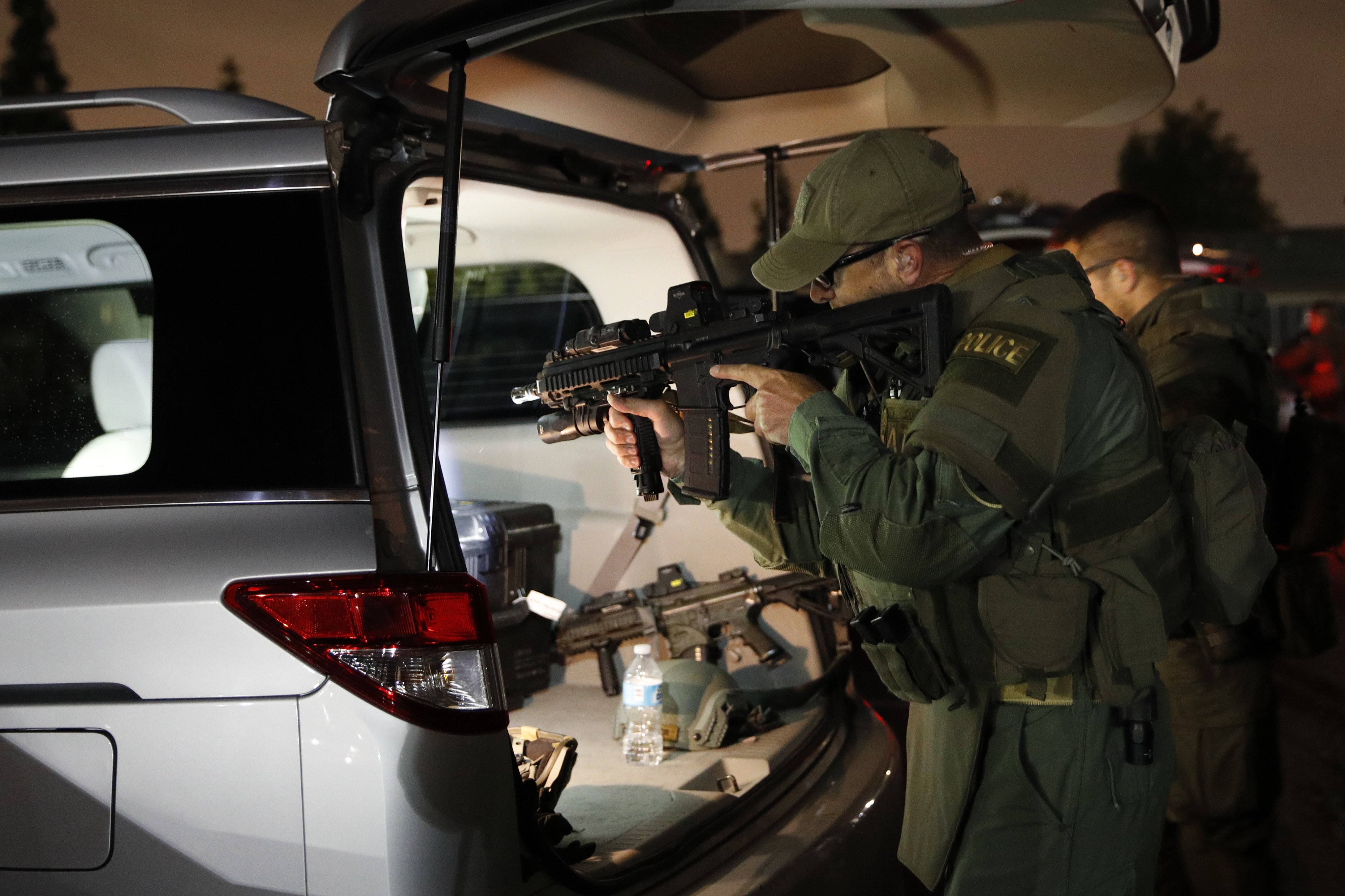 An ATF agent checks his weapon as he gets ready for a raid on May 17, 2017, in Los Angeles. Hundreds of federal and local law enforcement fanned out across Los Angeles, serving arrest and search warrants as part of a three-year investigation into the violent and brutal street gang MS-13.