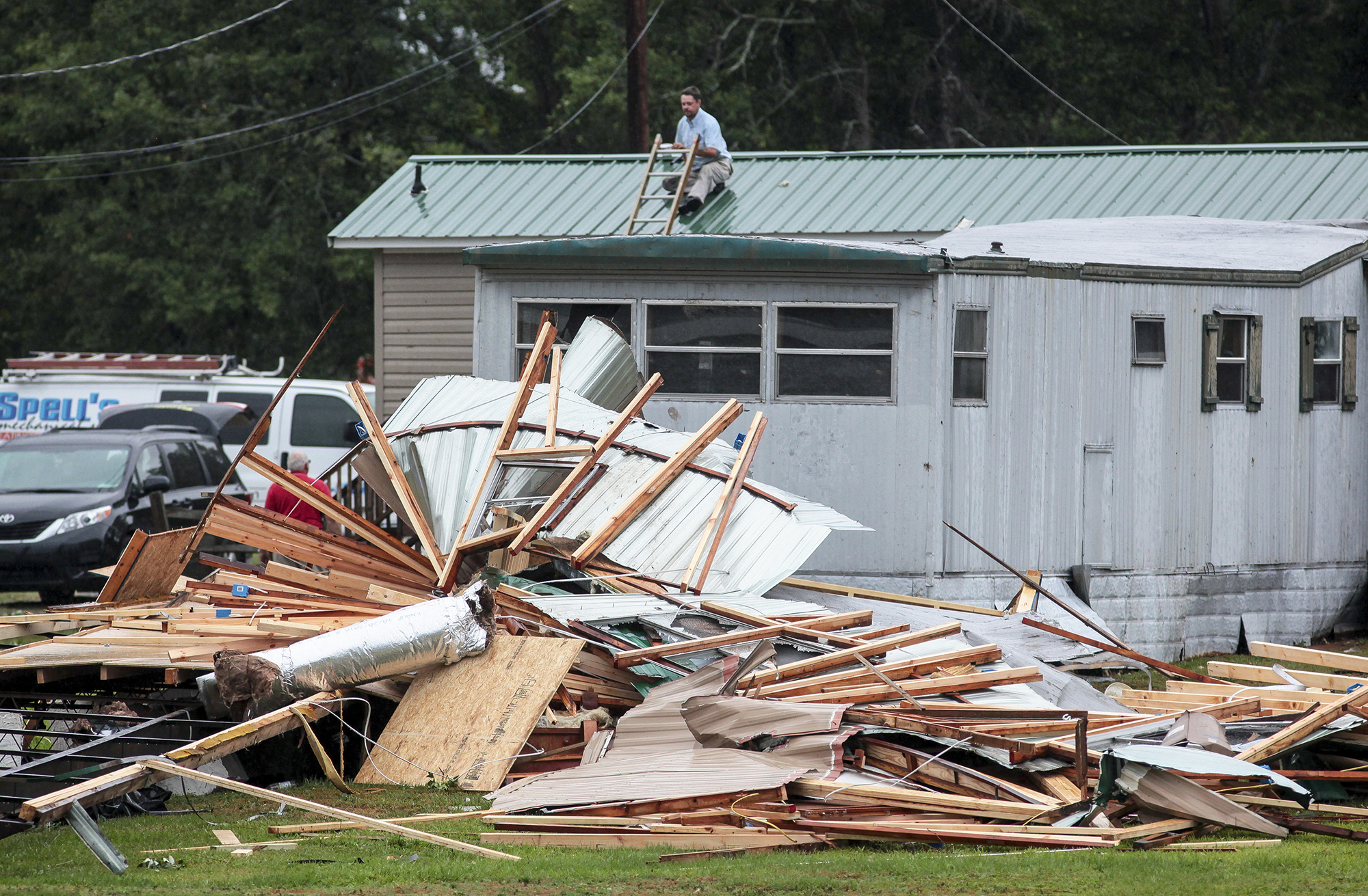 A man patches holes in his roof after a possible tornado destroyed parts of a mobile home neighborhood and a volunteer fire station in Autryville, N.C., on May 23, 2017.