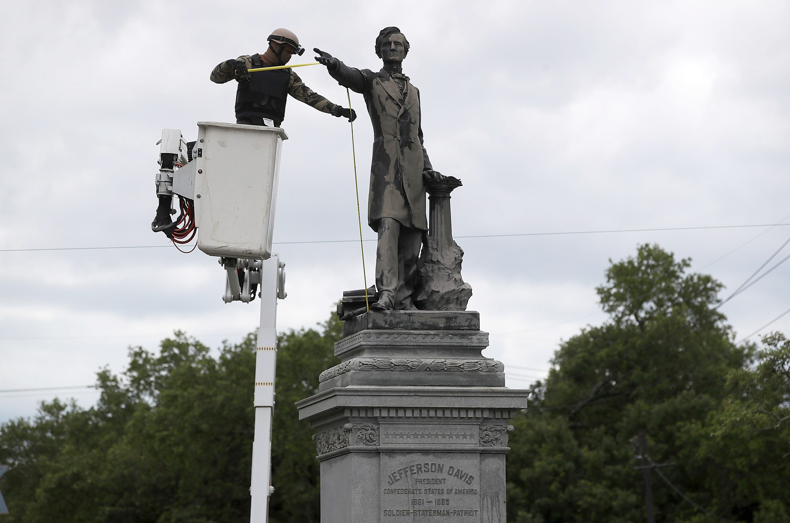 A worker in body armor measures New Orleans' Jefferson Davis monument for removal