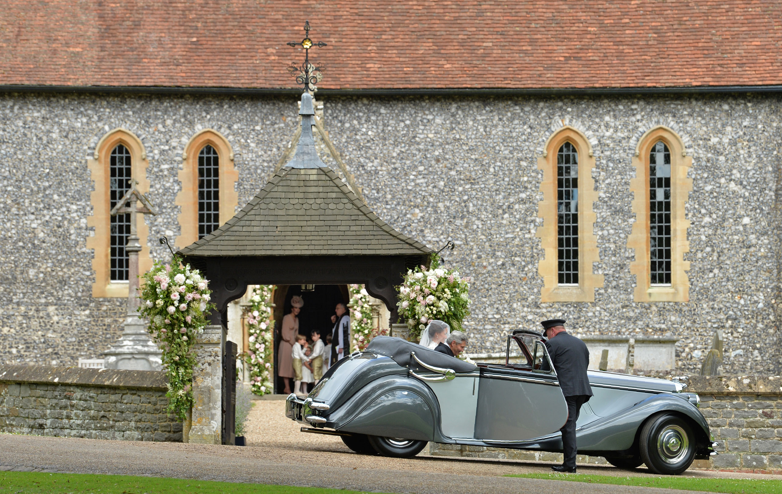 Catherine, Duchess of Cambridge stands with pageboys and bridesmaids in the doorway of St Mark's Church as her sister Pippa Middleton arrives with their father Michael Middleton in a vintage Jaguar for her wedding to James Matthews at St Mark's Church on May 20, 2017 in Englefield Green, England.