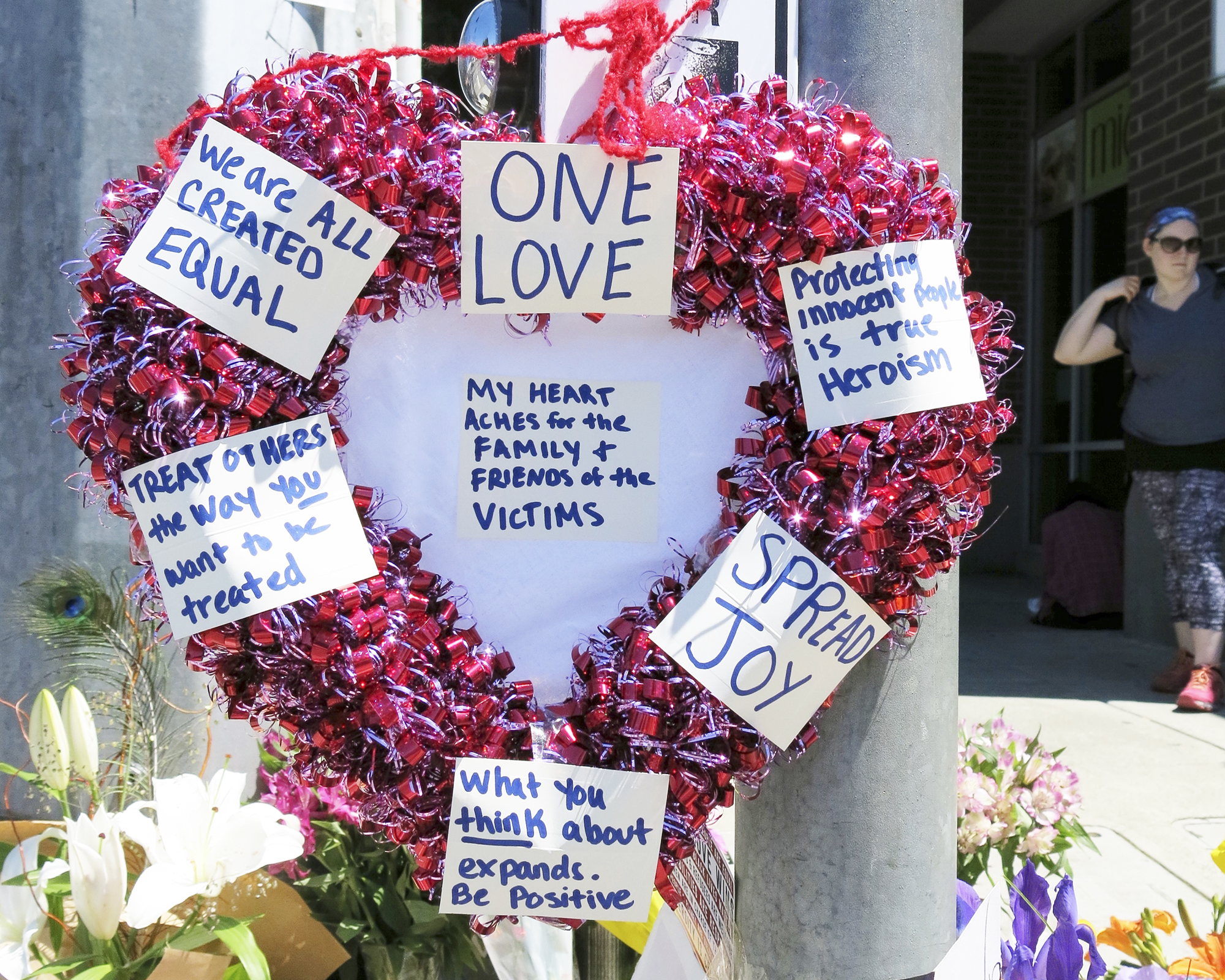 A heart-shaped wreath covered with positive messages hangs on a traffic light pole at a memorial in Portland, Ore, on May 27, 2017.