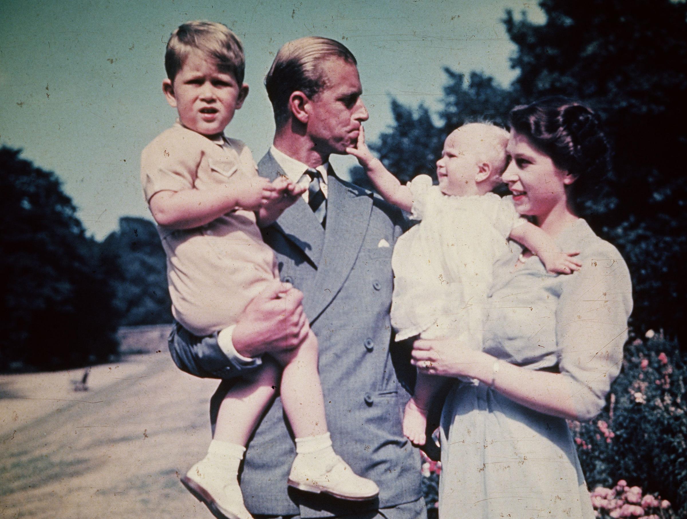The Duke of Edinburgh and Princess Elizabeth hold their children, Prince Charles and Princess Anne, Aug. 1951.