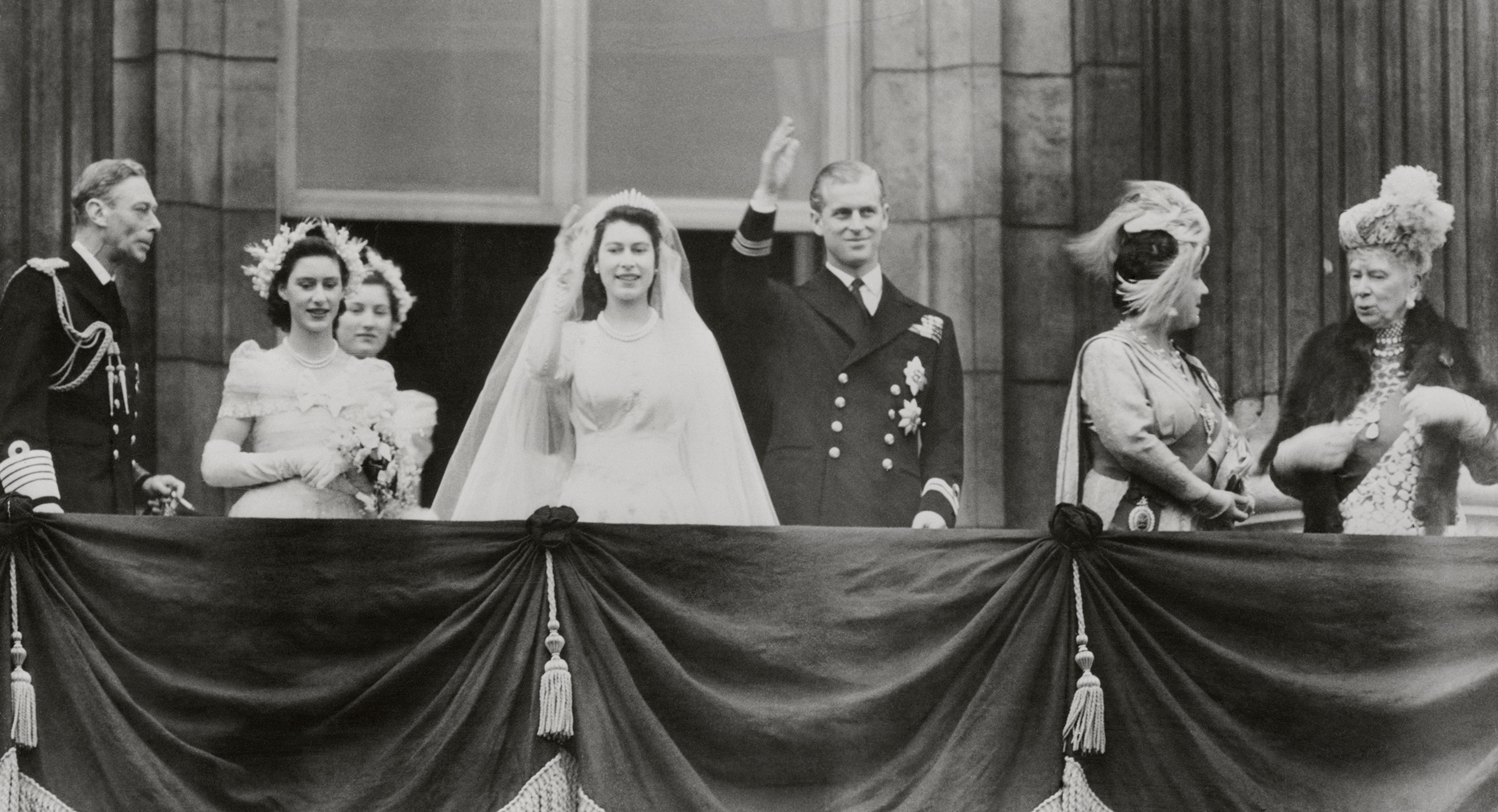 Princess Elizabeth and Philip Mountbatten, Duke of Edinburgh, wave from a balcony at Buckingham Palace in London, shortly after their wedding on Nov. 20, 1947.