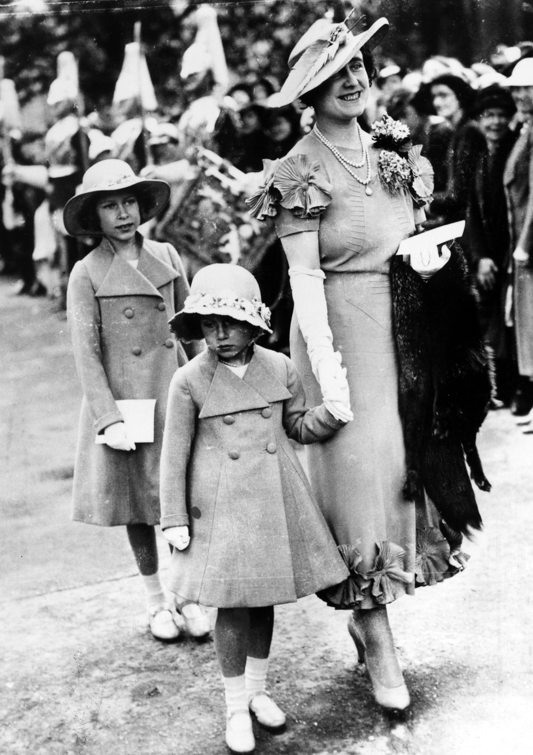 Queen consort Elizabeth holding Princess Margaret's hand as Princess Elizabeth follows, attending the Elphinstone wedding, 1936.