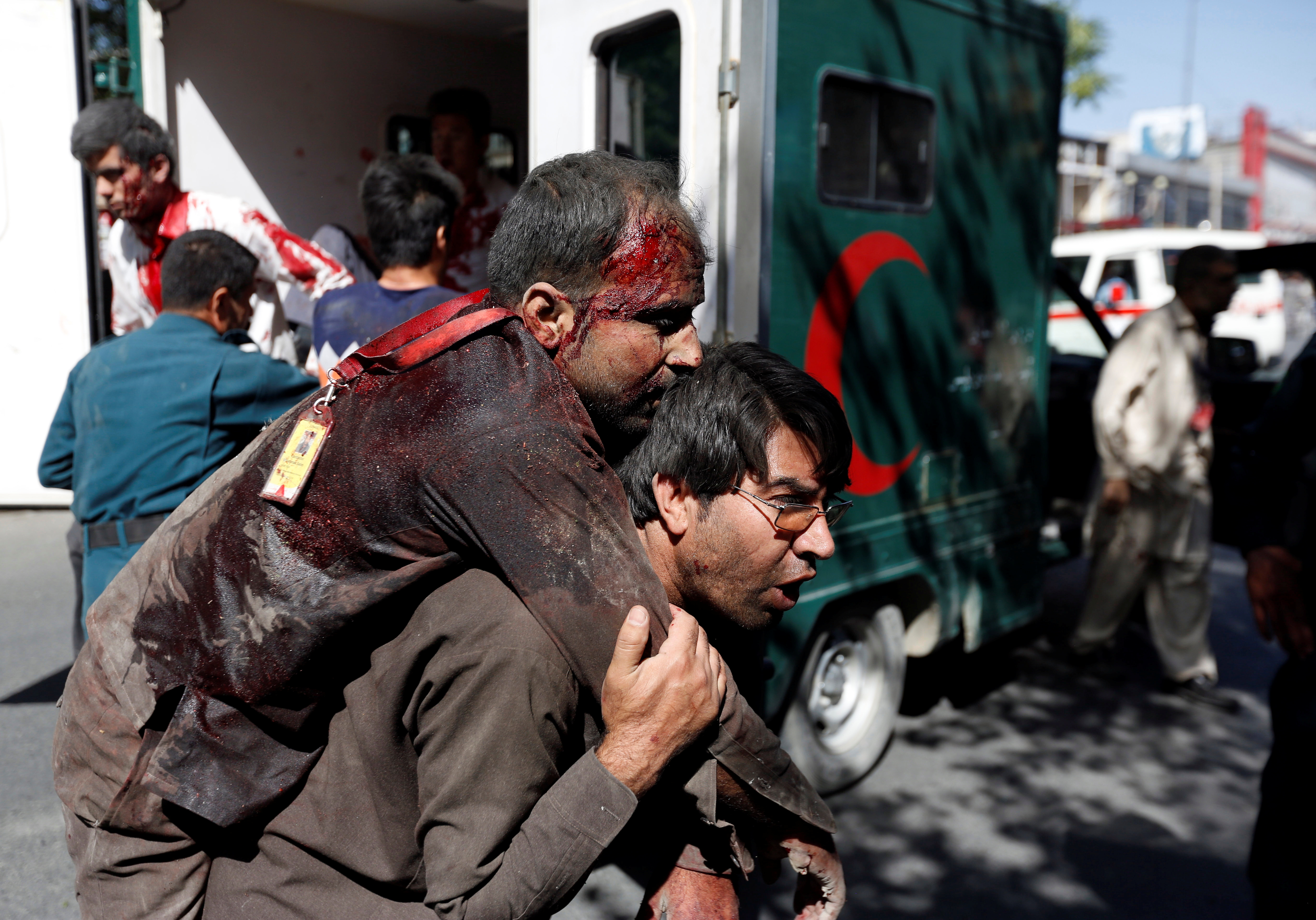An Afghan man carries an injured man to a hospital after a blast in Kabul, May 31, 2017.