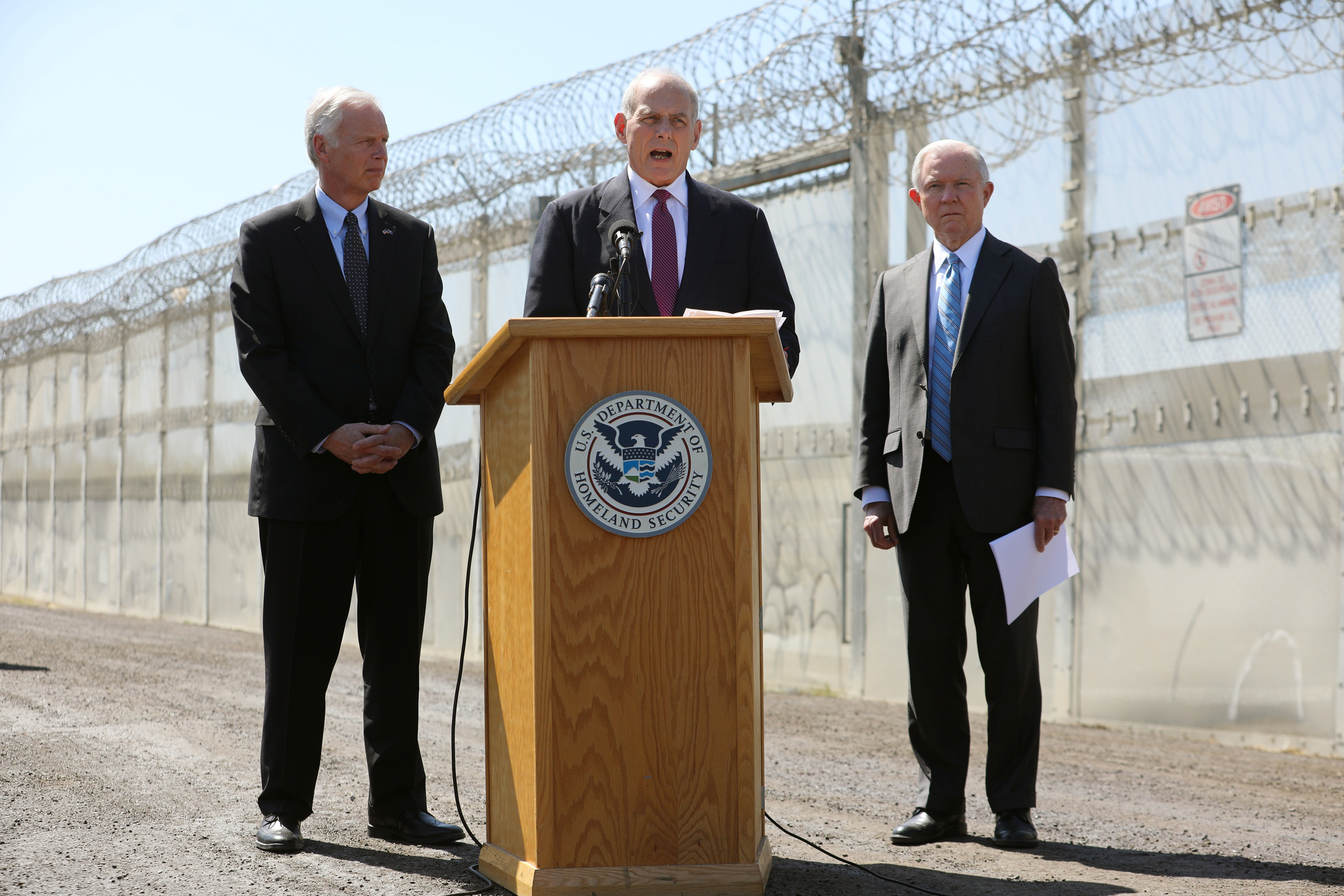 Secretary of Homeland Security John Kelly speaks as Attorney General Jeff Sessions and U.S. Senator Ron Johnson, Chairman of the Senate Committee on Homeland Security and Governmental Affairs listen during visit to the U.S. Mexico border fence in San Diego on April 21, 2017.