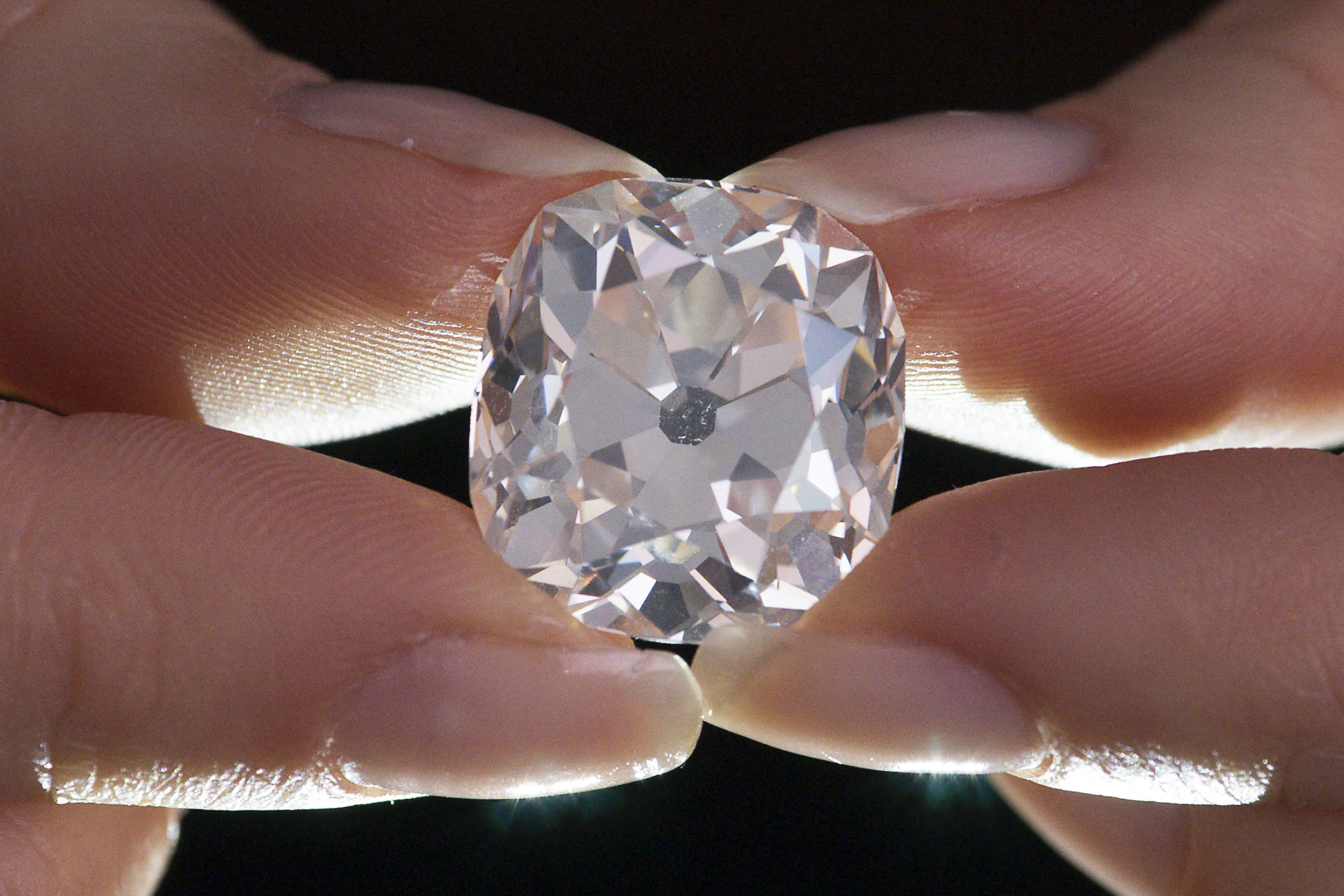 A member of Sotheby's staff poses holding a 26.27 carat, cushion-shaped, white diamond, for sale at Sotheby's auction house in London.
