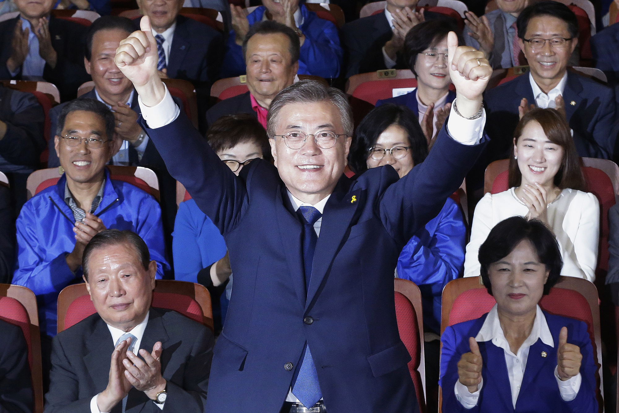 Moon Jae-in raises his hands as his party leaders and members watch local media's results of exit polls for the presidential election in Seoul, South Korea,on May 9, 2017.