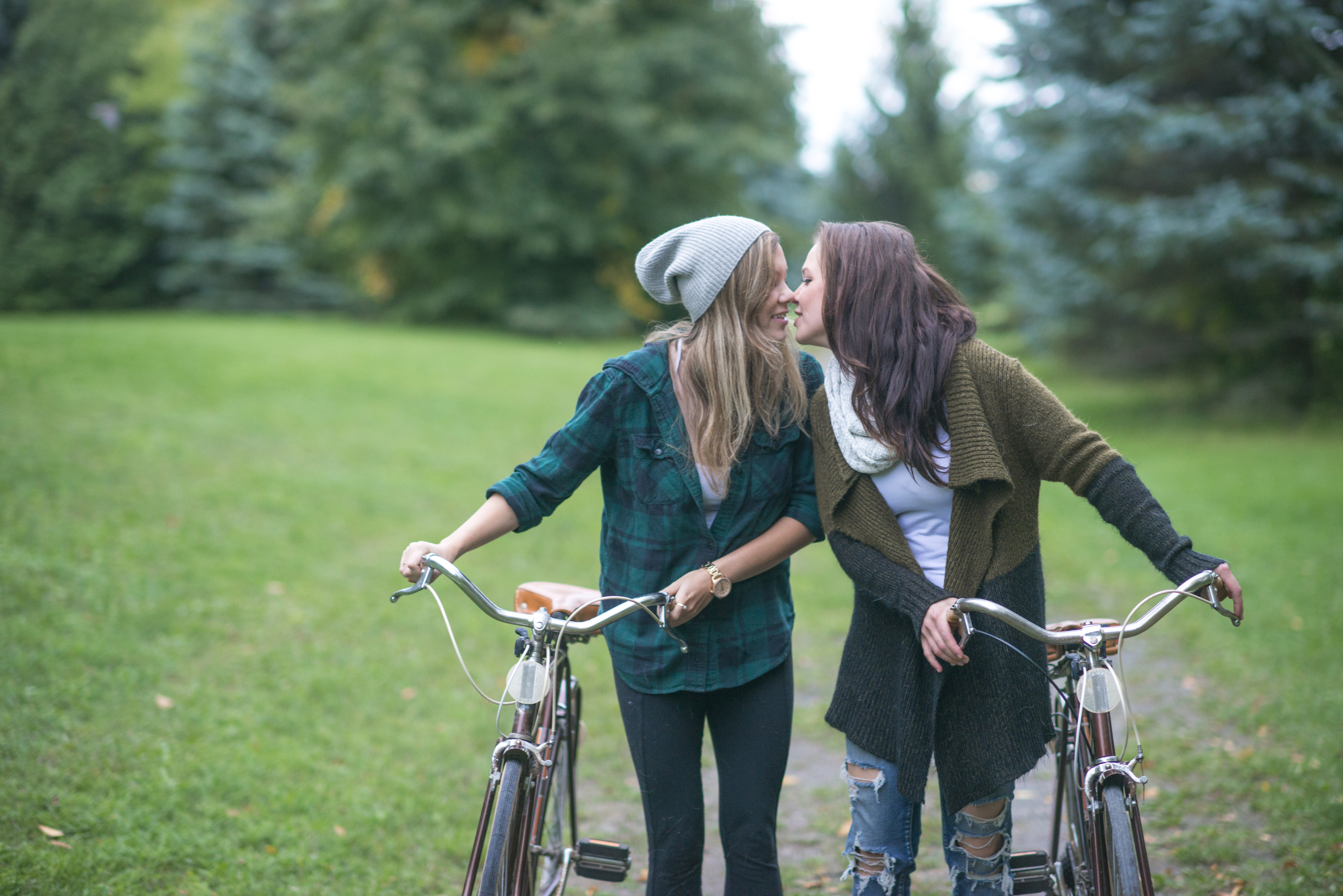 A female lesbian couple is spending time together outside in nature. They are kissing before going on a bike ride.
