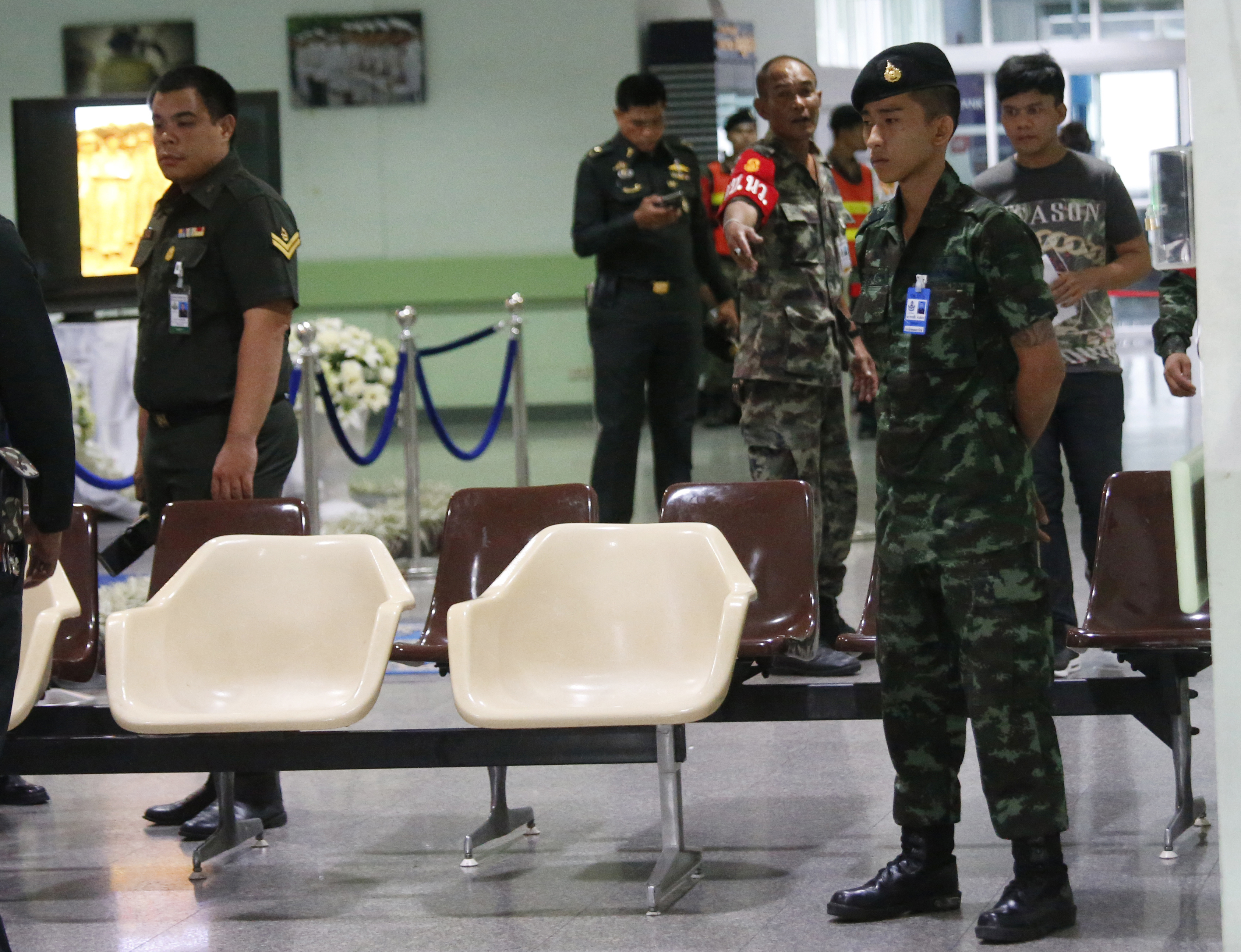 A Thai soldier stands guard as police officers investigate the lobby of Phramongkutklao Hospital, a military-owned hospital that is also open to civilians, in Bangkok after a bomb wounded more than 20 people, in Bangkok Monday, May 22, 2017.