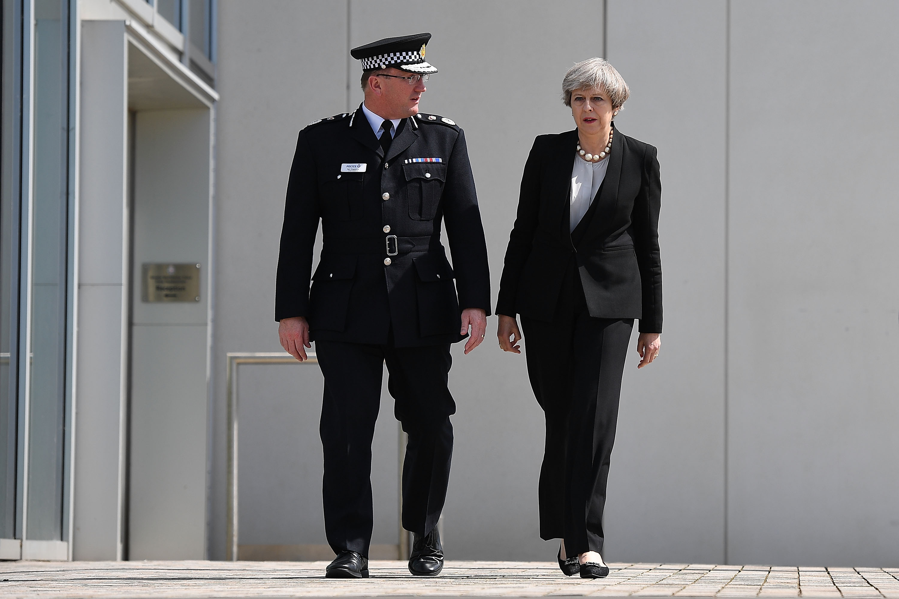 Britain's Prime Minister Theresa May talks with Chief Constable of Greater Manchester Police Ian Hopkins as they leave the Greater Manchester Police station on May 23, 2017 in Manchester, England.