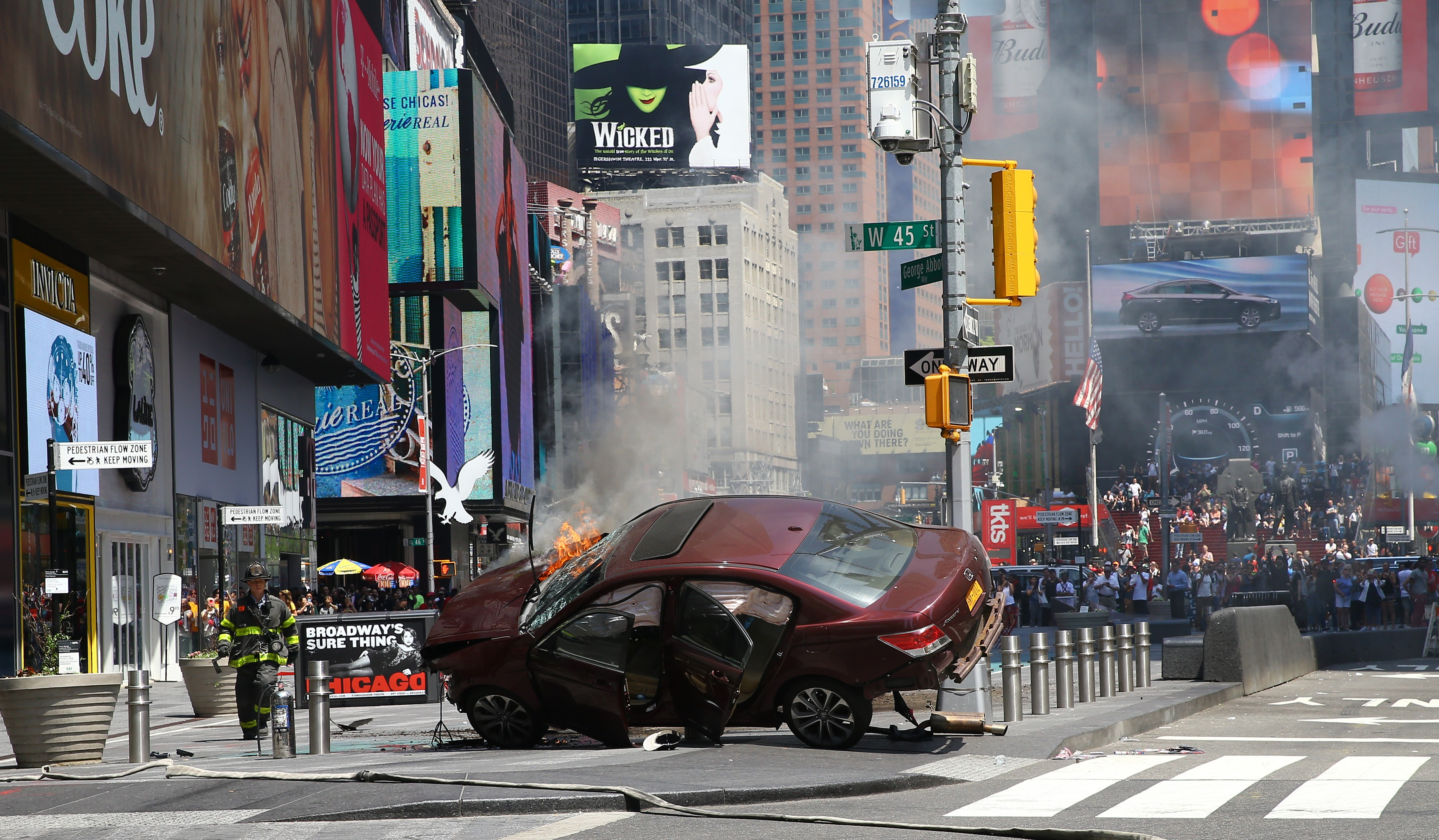 Flames and smoke rise from a wrecked vehicle after it plowed into pedestrians on a busy sidewalk on the corner of West 45th St. and Broadway at Times Square in New York on May 18, 2017.