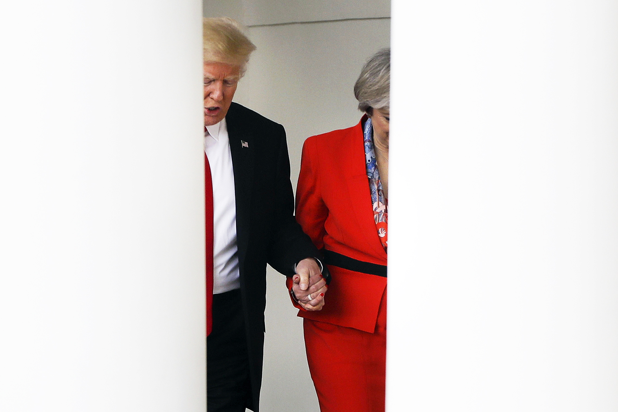 Donald Trump holds hands with British Prime Minister Theresa May, as they walk along the colonnade of the White House in Washington, D.C., on Jan. 27, 2017.
