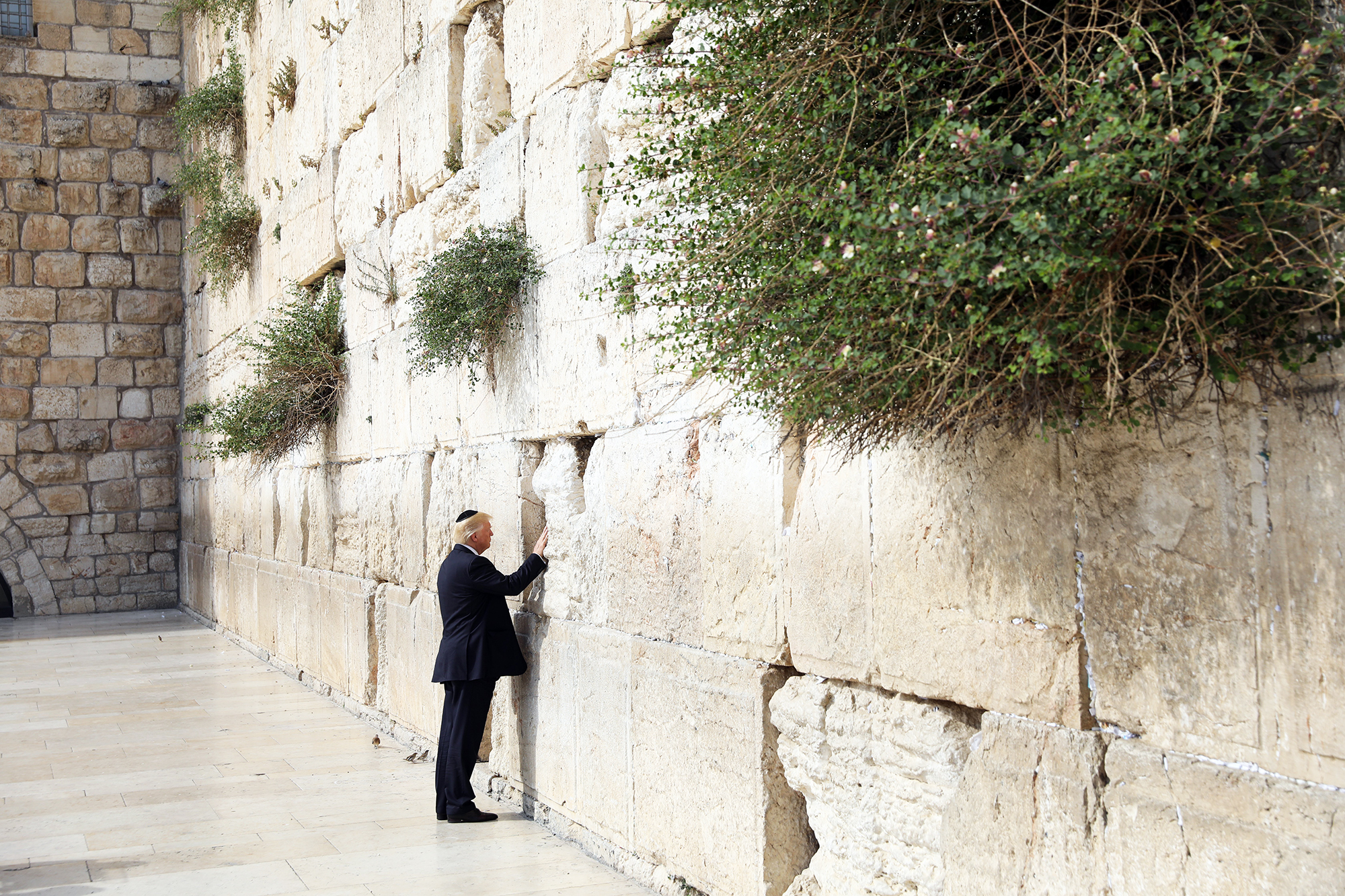 Donald Trump touches the Western Wall, Judaism's holiest prayer site, in Jerusalem's Old City, on May 22, 2017.