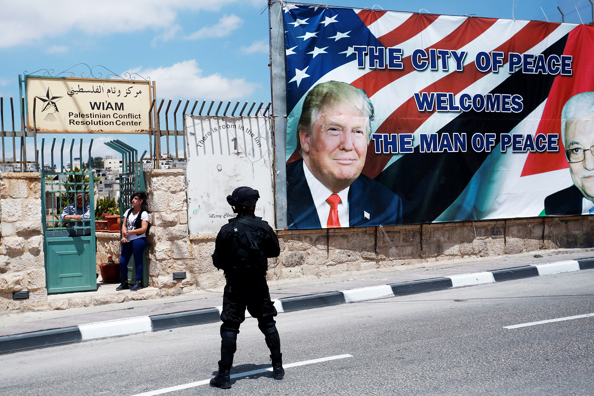 A soldier stands guard over a route as people watch Donald Trump's motorcade carry him back to Jerusalem after his meeting with Palestinian Authority President Mahmoud Abbas in the West Bank city of Bethlehem, on May 23, 2017.