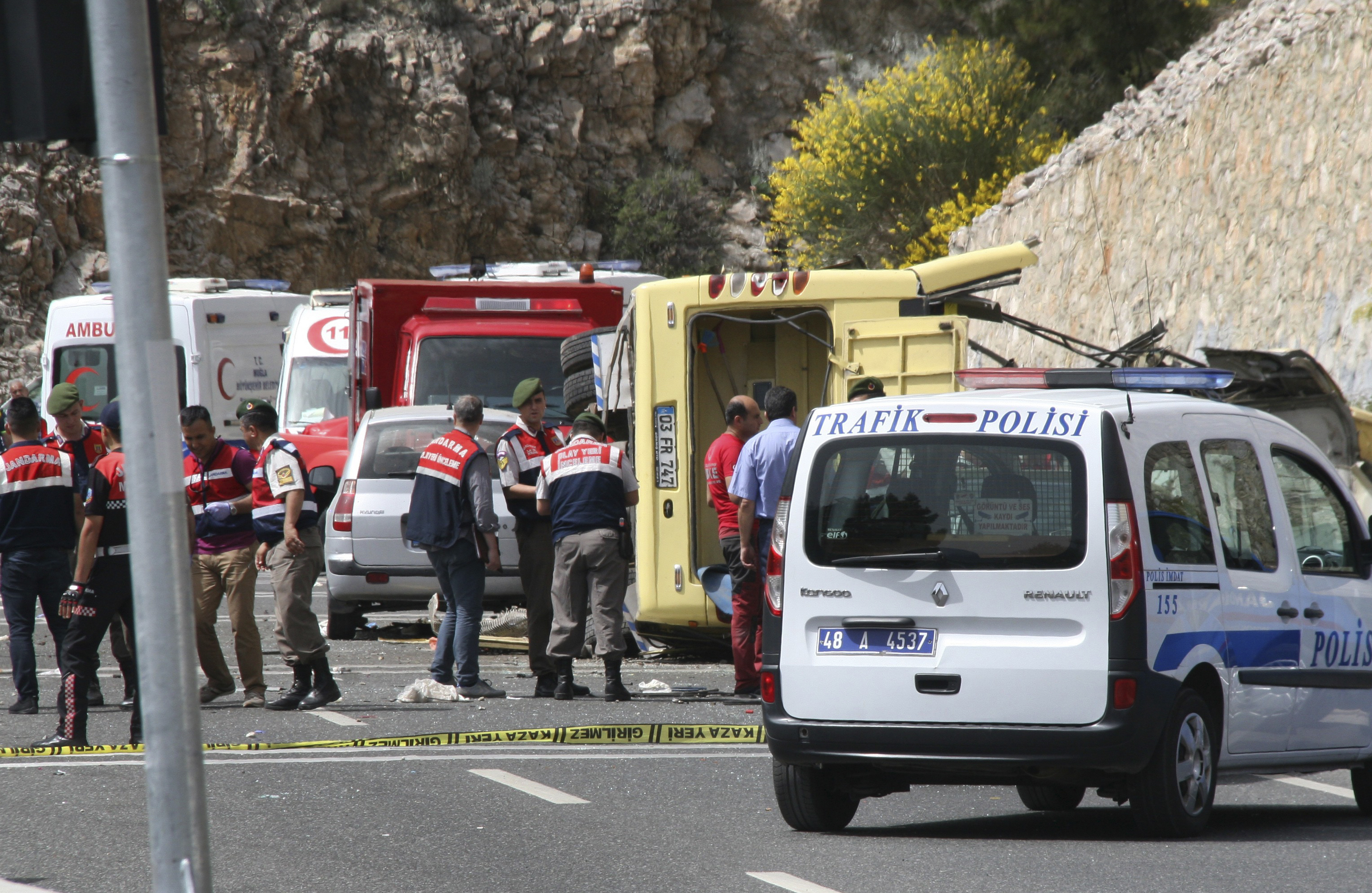 Turkish police officers work next to an overturned bus at the scene of a traffic accident, near Marmaris, western Turkey, on May 13, 2017.