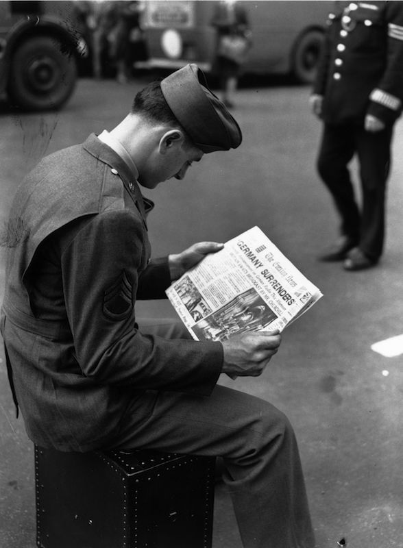 An American soldier in London reads the news of the German surrender at the end of World War II.