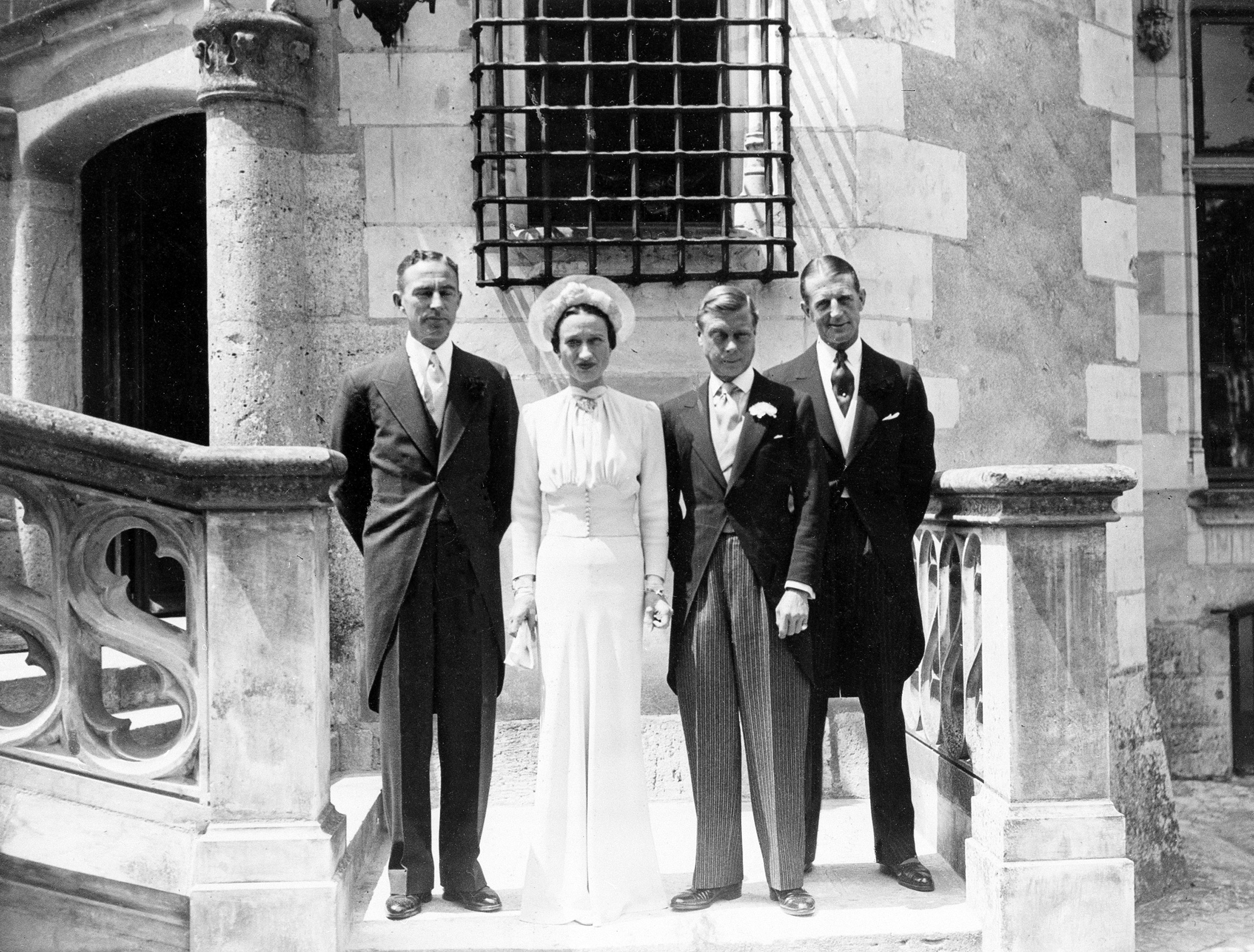 The Duke and Duchess of Windsor pose on the castle steps after their wedding at Chateau de Cande near Tours, France, on June 3, 1937.  At left is Hermann Rogers Winters and at right is Major Metcalf, first former King of England's witness.  The floor-length silk gown worn by the Duchess is designed by Mainbocher.