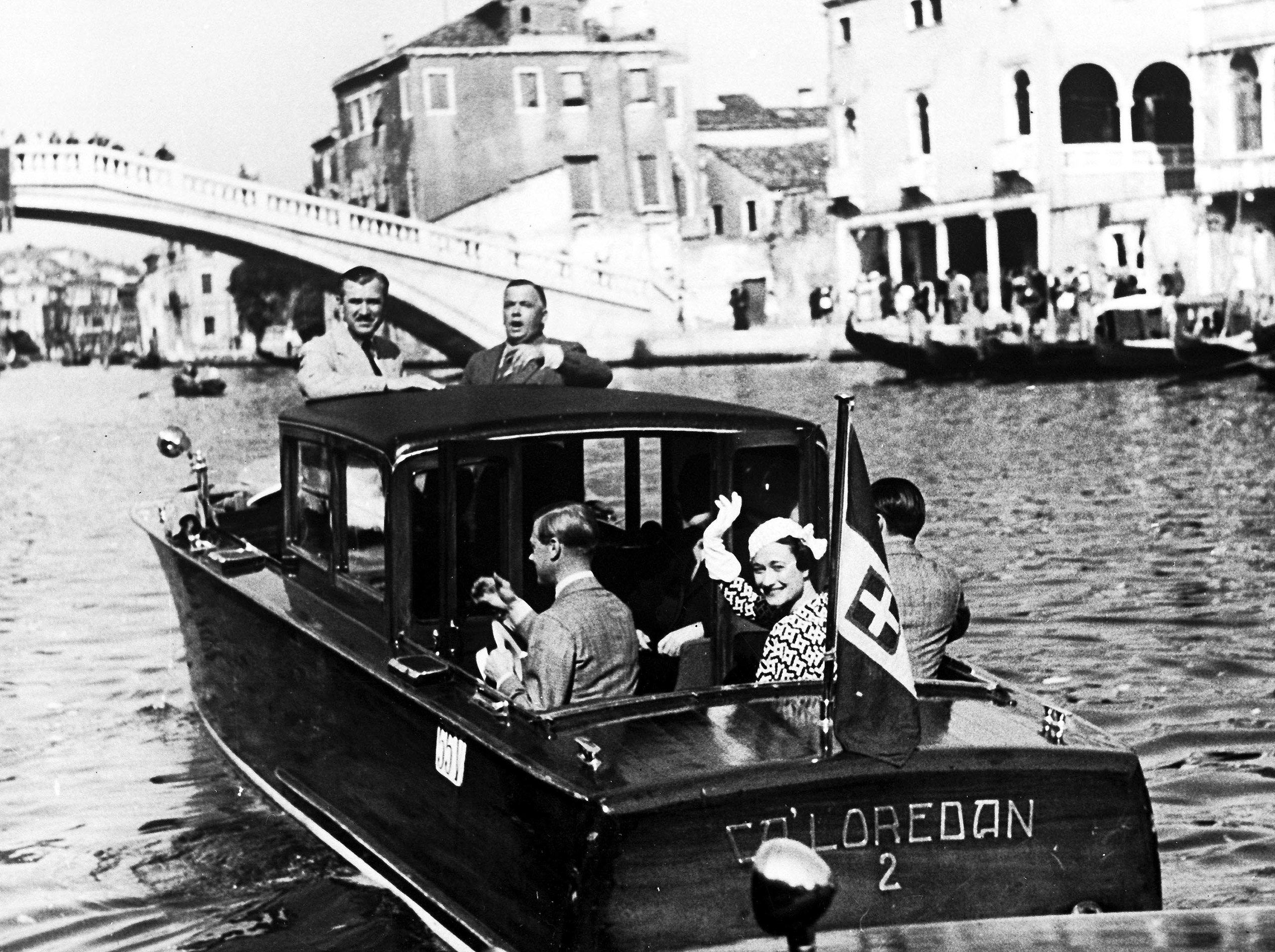 The Duke and Duchess of Windsor in a motor boat on one of the canals in Venice, Italy, June 4, 1937, wave to onlookers as they are taken to their hotel.
