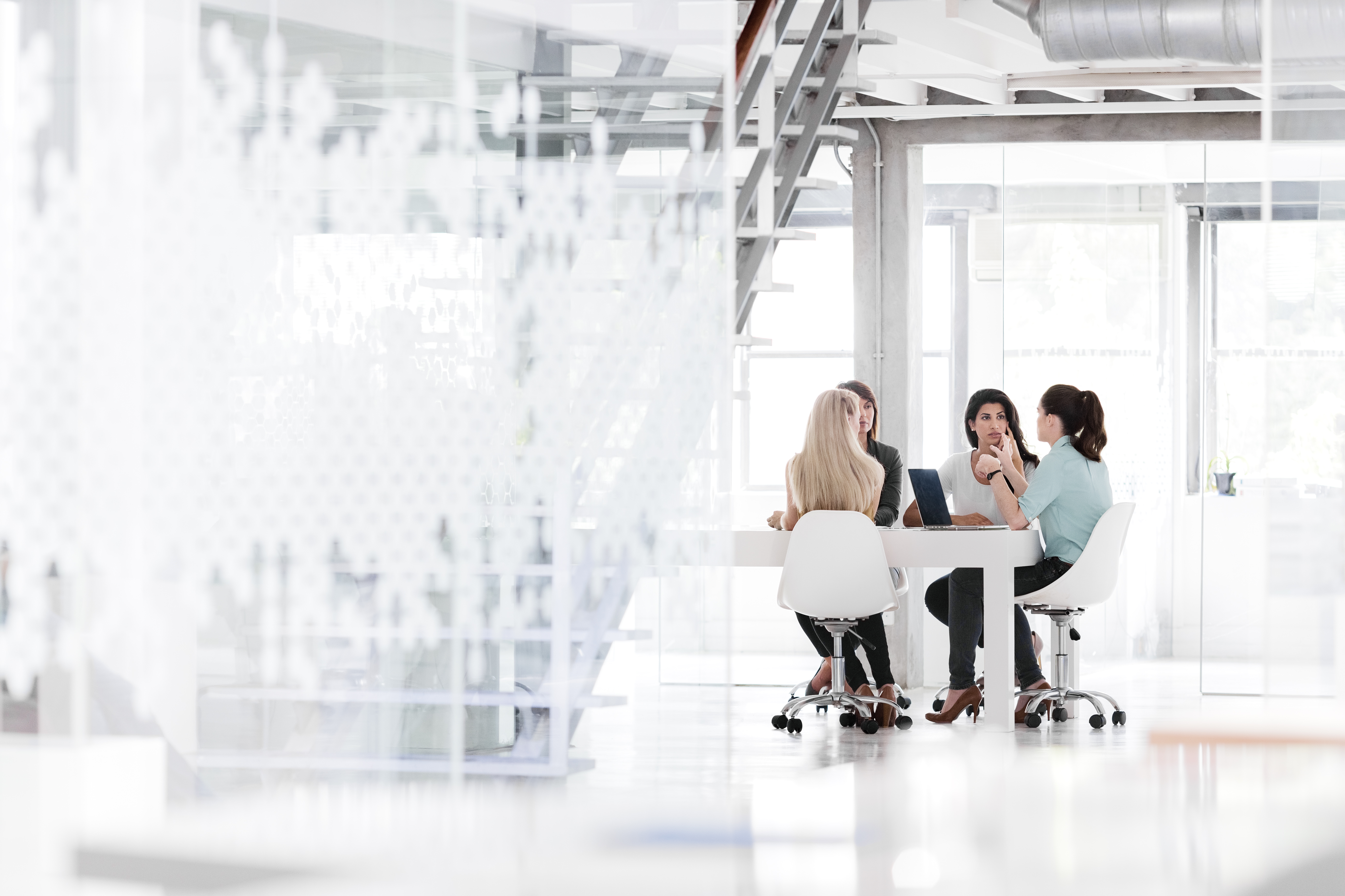 Women in a business meeting in a bright and modern office space.