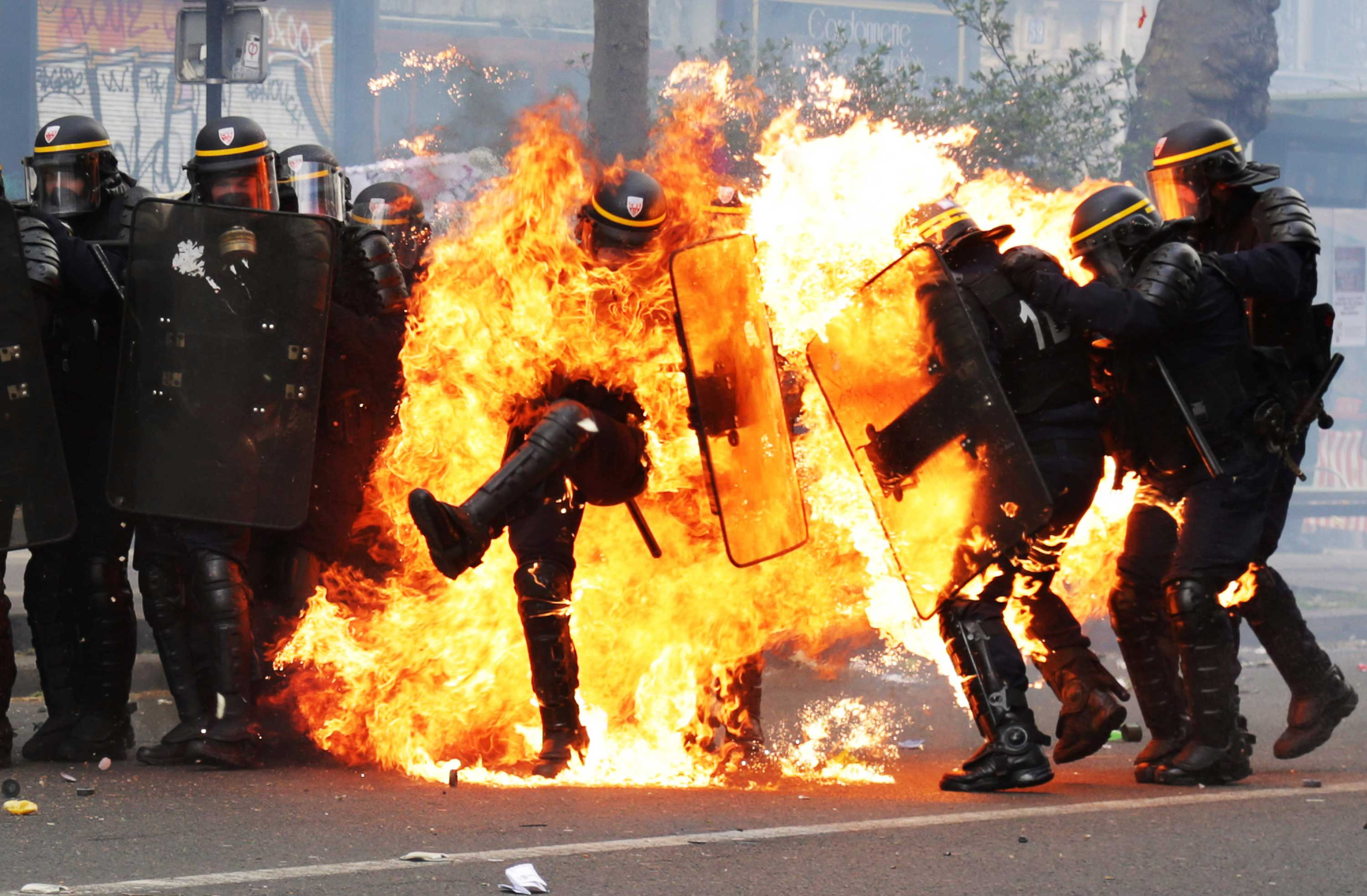 French CRS anti-riot police officers are engulfed in flames as they face protesters during a march for the annual May Day workers' rally in Paris on May 1, 2017.