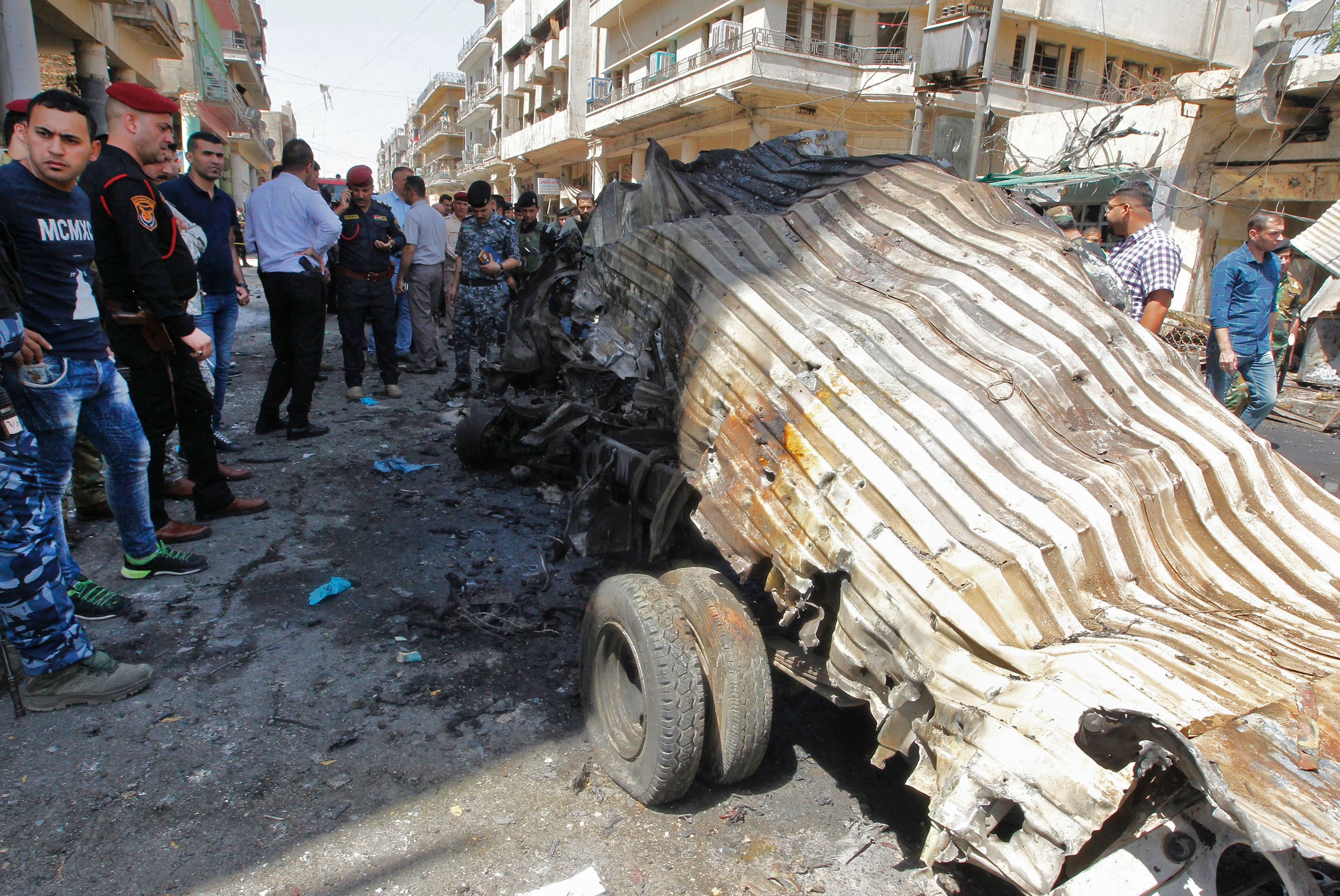 EDITORS NOTE: Graphic content / Iraqis gather at the site of a car bomb explosion near Baghdad's  Al-Shuhada Bridge on May 30, 2017 which killed at least five people and wounded 17, security and medical officials said.