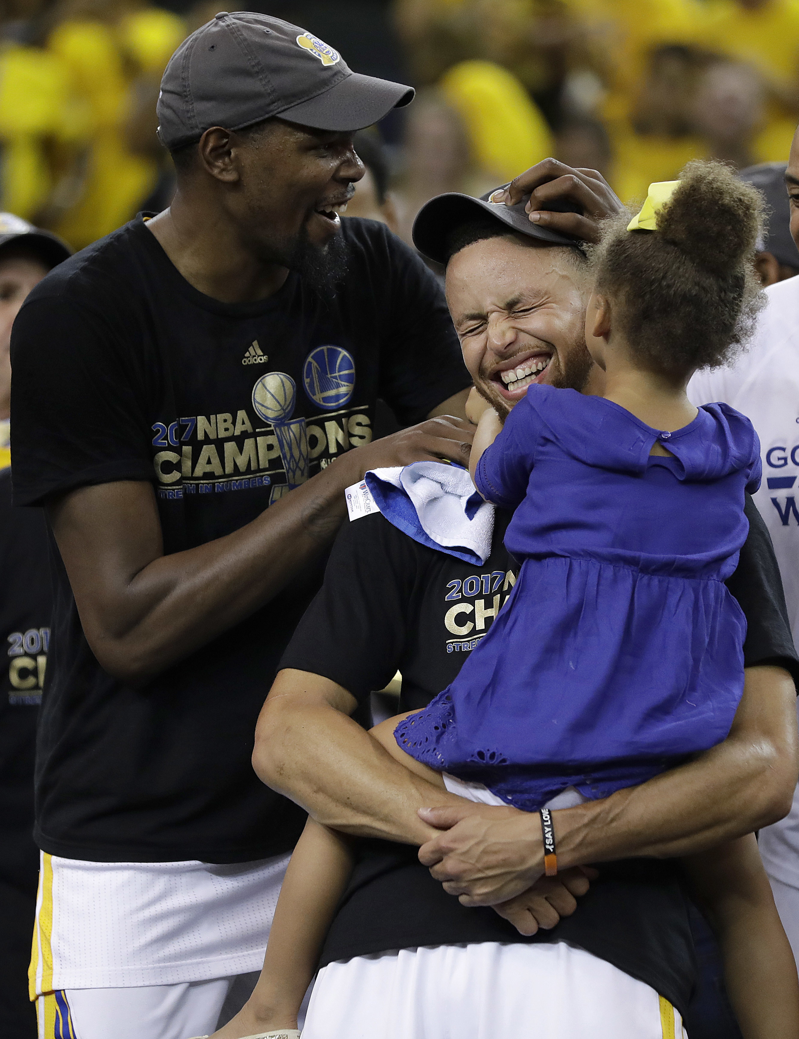 Golden State Warriors guard Stephen Curry, center, holds his daughter Riley as they celebrate with forward Kevin Durant, left, after Game 5 of basketball's NBA Finals against the Cleveland Cavaliers in Oakland, Calif., Monday, June 12, 2017.