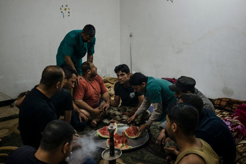 Ahmad (center) tries to resist laughing while the rest of the ISOF medics joke around after a long day of treating the wounded during the battle for Mosul, Iraq, on April 18, 2017.