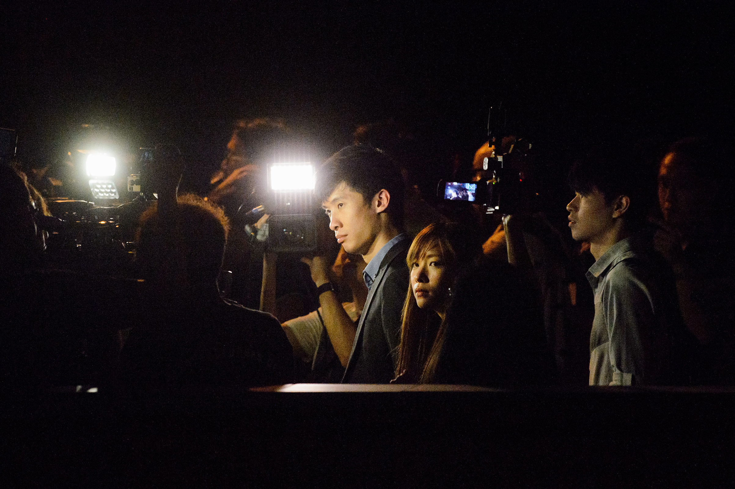 """Baggio Leung (center left) and Yau Wai-ching (center right) are surrounded by media as they leave the High Court after a news conference in Hong Kong on Nov. 15, 2016. The two activists were elected to the territory's legislature on an unprecedented pro-independence platform but were prevented from taking up their seats after they pledged allegiance to the """"Hong Kong nation"""" at their swearing-in ceremonies, instead of to China and the Hong Kong Special Administrative Region as defined under the territory's constitution."""