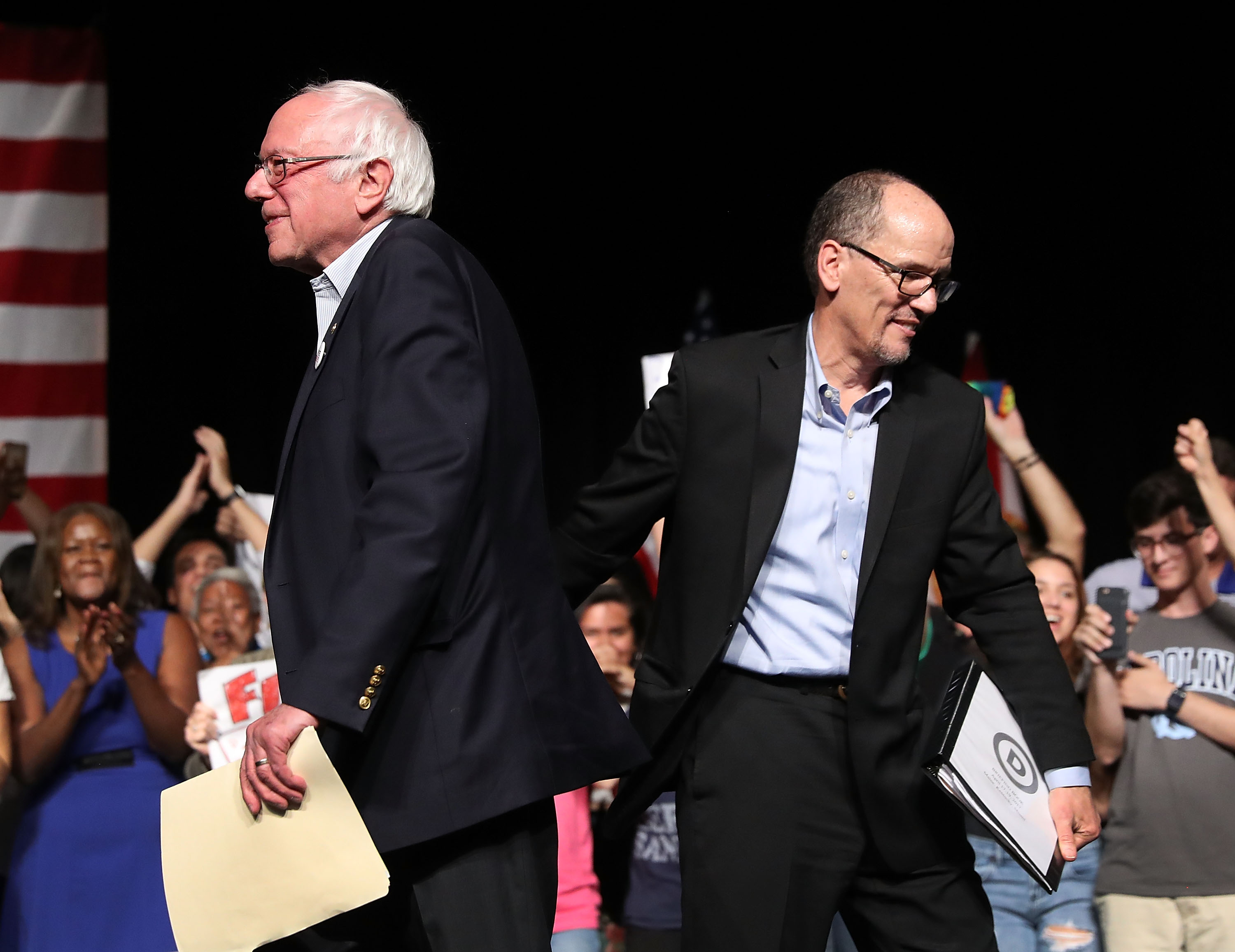 Sen. Bernie Sanders (I-VT) and DNC Chair Tom Perez walk past each other as Sen. Sanders takes to the stage to speak during their  Come Together and Fight Back  tour at the James L Knight Center on April 19, 2017 in Miami, Florida.