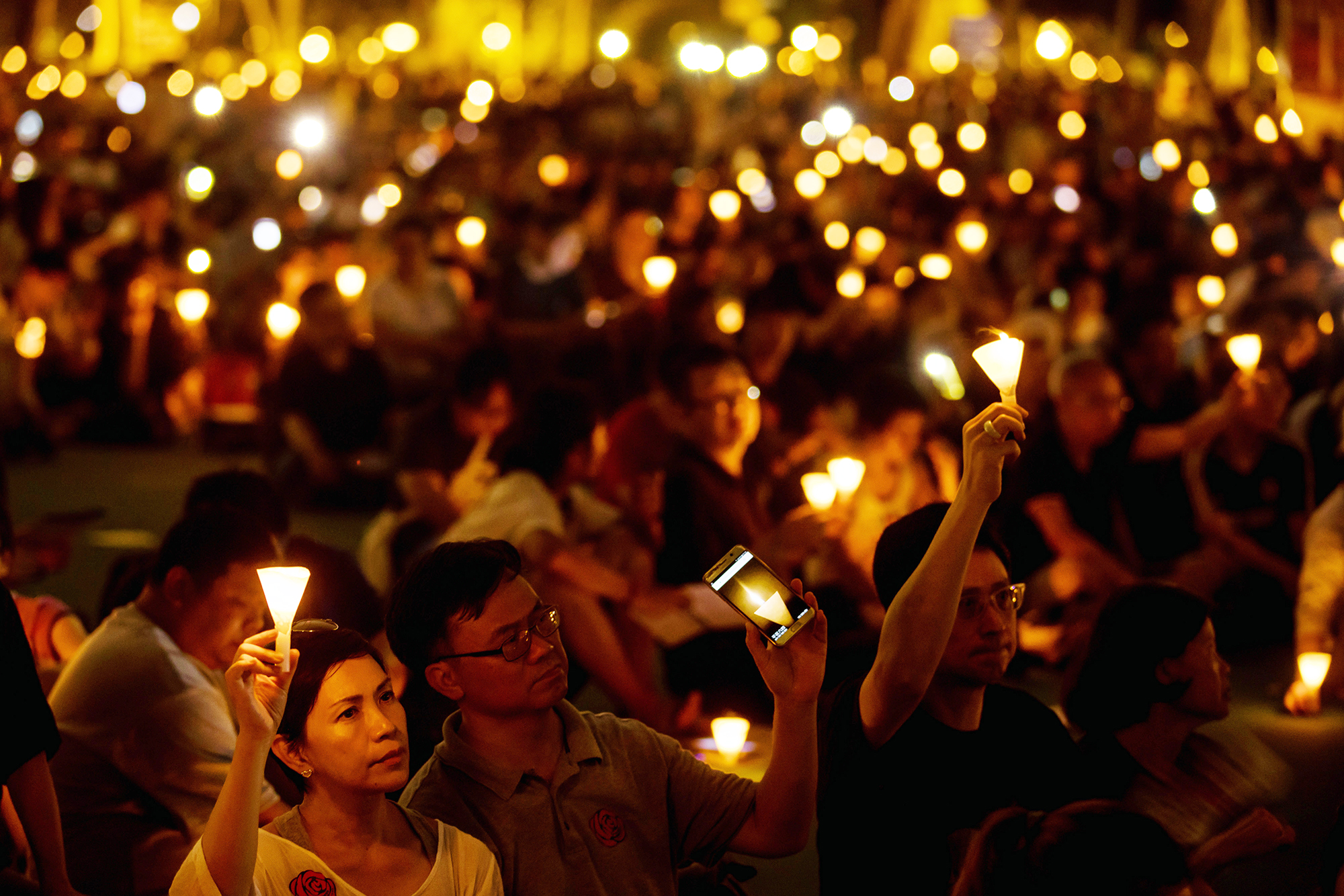 Demonstrators attend a candlelight vigil at Victoria Park in Hong Kong, on June 4, 2017.