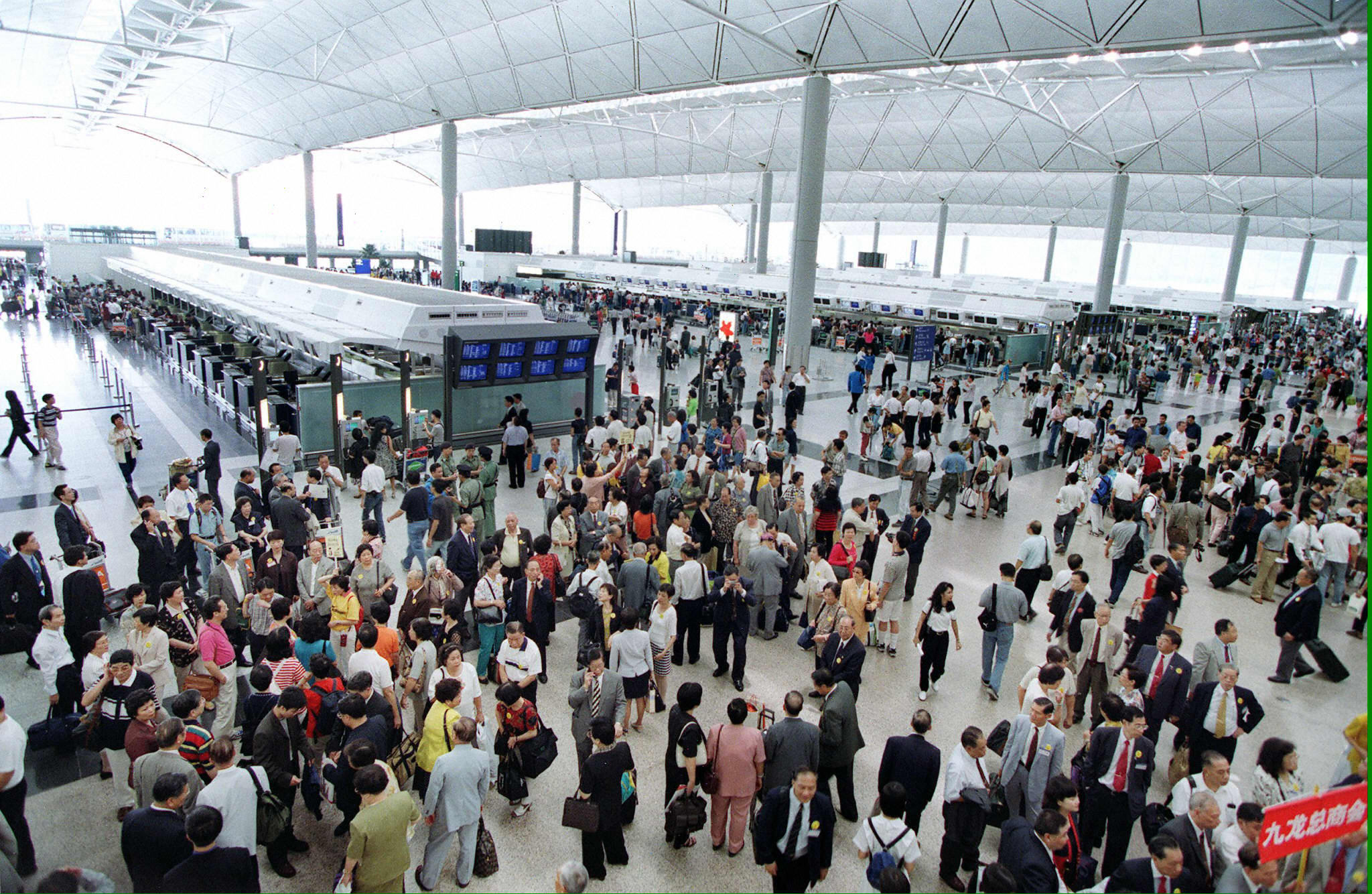 People crowd near the check-in counters at the departure level of the state-of-the-art Hong Kong International airport on July 6, 1998, the airport's first day of commercial operations. Designed as a showpiece of the new, post-handover Hong Kong, the airport was plagued by several months of technical glitches but recovered to become a facility that is consistently ranked among the world's best.