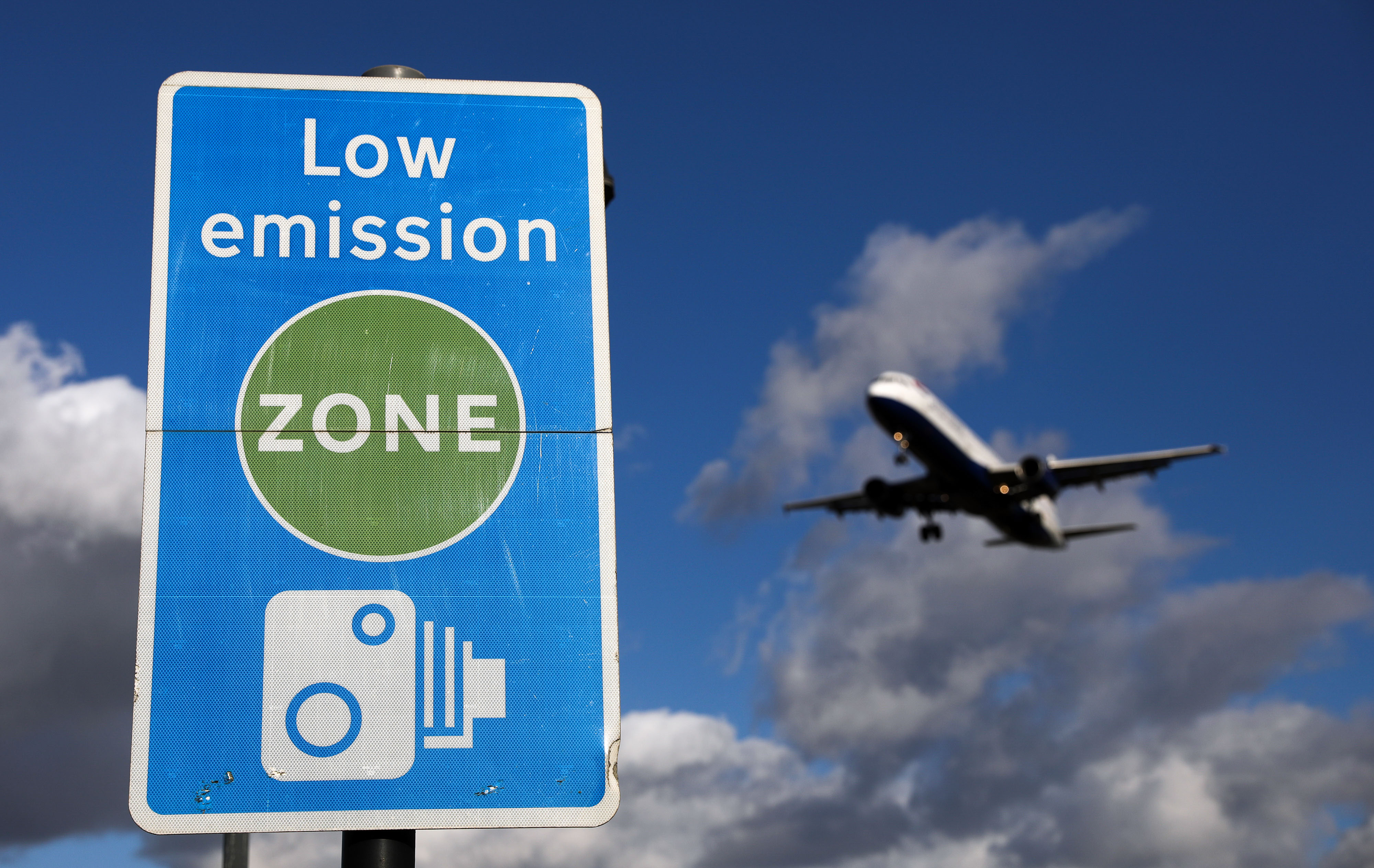 An aircraft operated by British Airways passes a low emission zone sign as it prepares to land at Heathrow airport, in London in October.