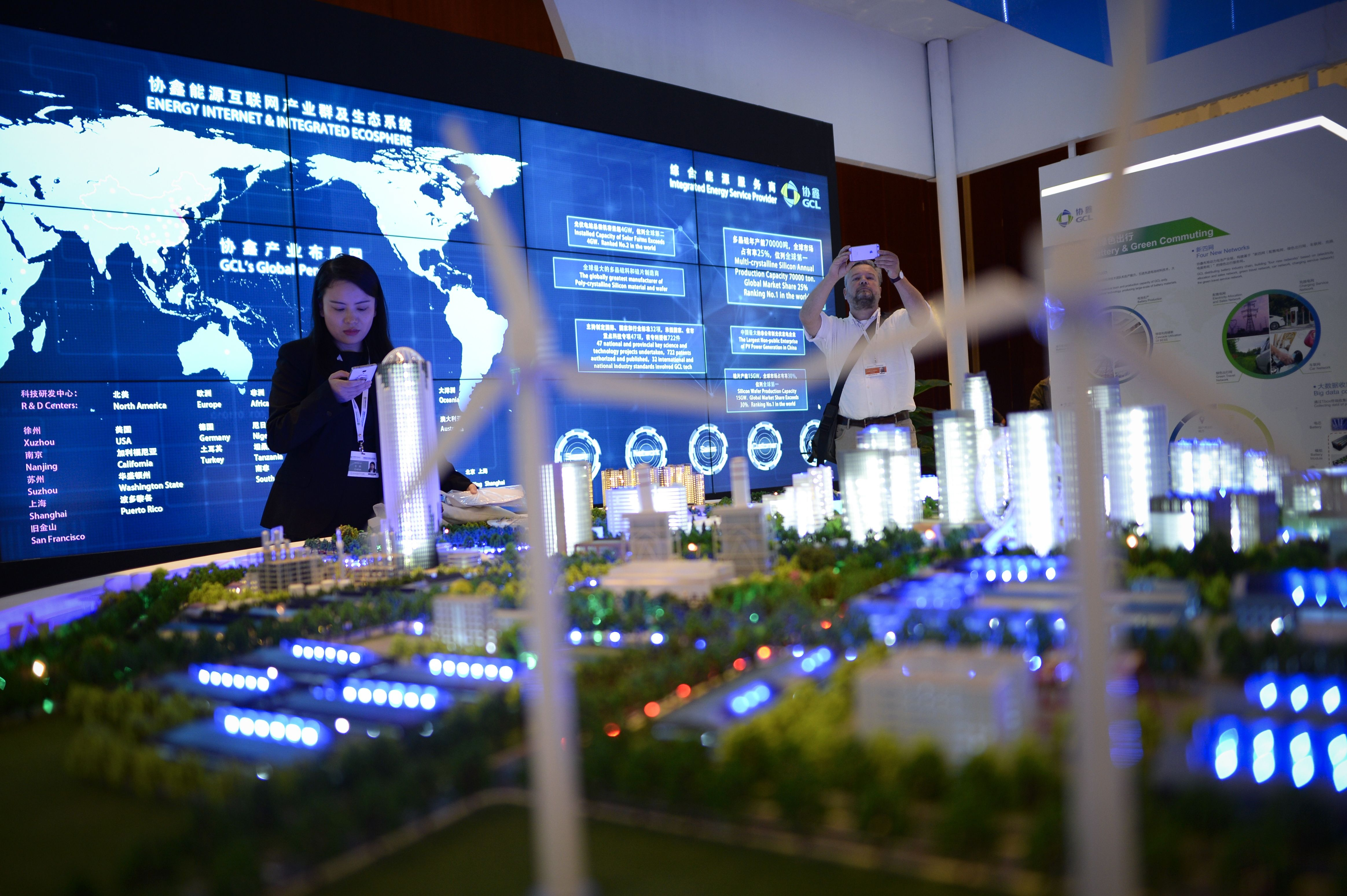People visit a clean energy exhibition on the sidelines of the Clean Energy Ministerial international forum in Beijing on June 6, 2017.                     Officials and business leaders from around the world have gathered for the clean energy ministerial meeting in the Chinese capital.