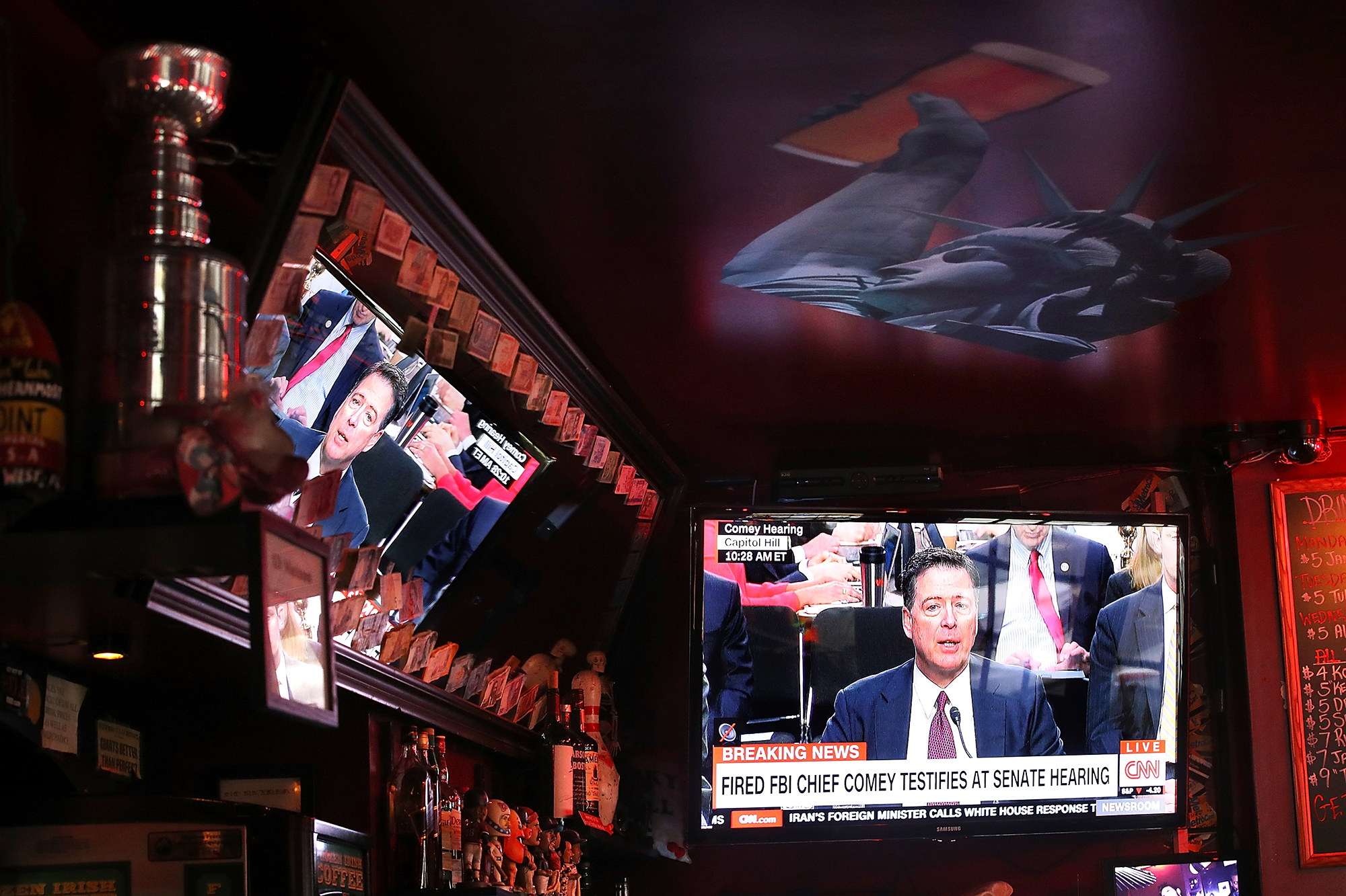 A television broadcast of former FBI Director James Comey testimony before the Senate Intelligence Committee plays at Ace's Bar, on June 8, 2017 in San Francisco.