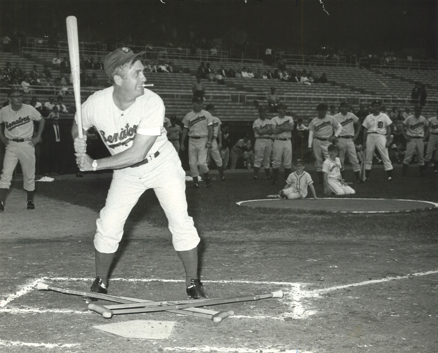 Silvio O. Conte, R-Mass., with a cigar clamped in his teeth and his recently discarded crutches below him, lines up to take a Democrat team pitch at the 1966 Congressional Baseball game.