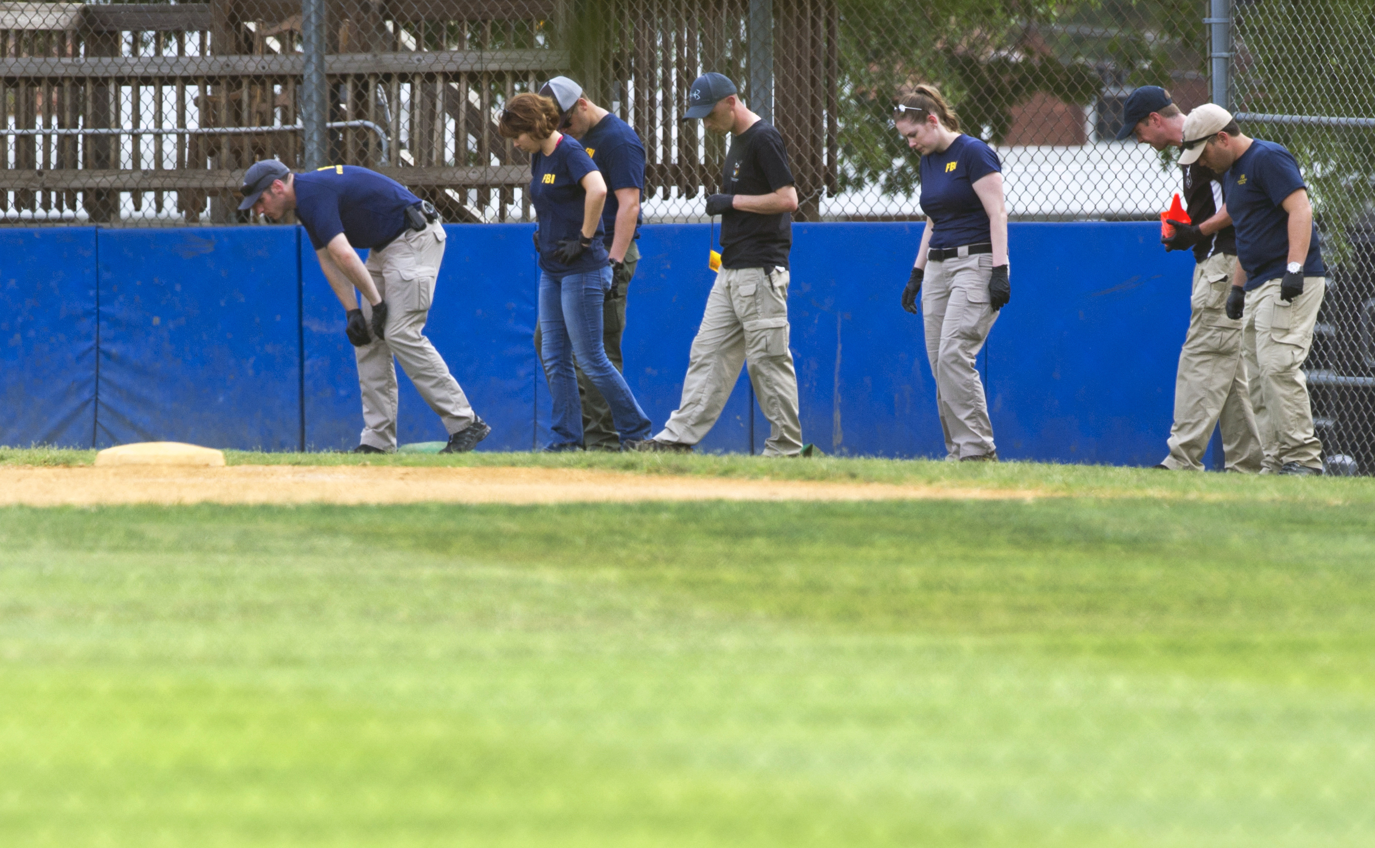 The FBI Evidence Response Team inspects the third base side of the baseball field in Alexandria, Va., June 14, 2017, where a rifle-wielding attacker opened fire on Republican lawmakers at a congressional baseball practice.