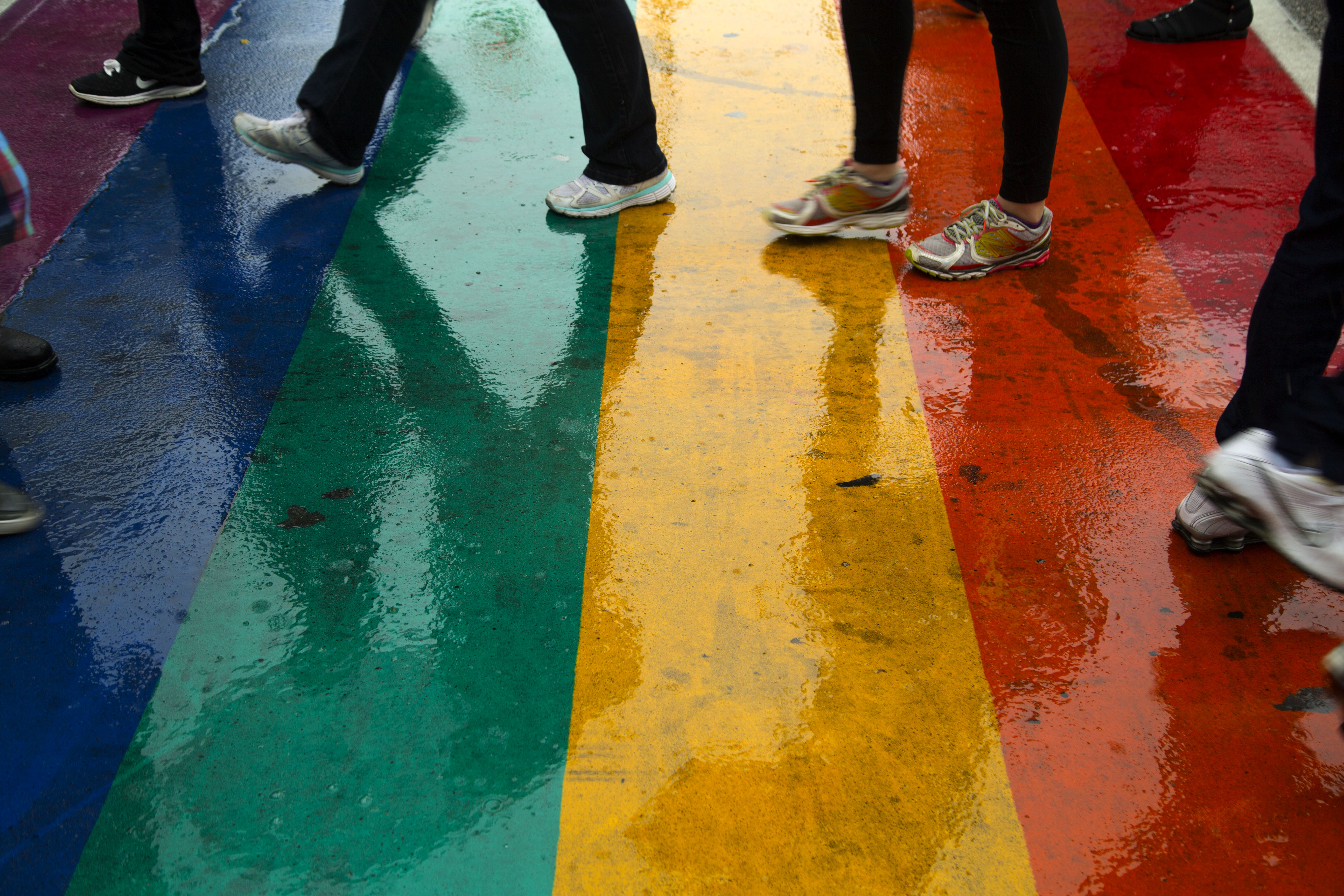 The rainbow painted  crosswalks on Church Street reflect the feet of passersby after heavy rain. Participants in the Toronto Dyke March did not let the heavy rainfall dampen their spirits during Pride Toronto 2015. JUNE 27, 2015.