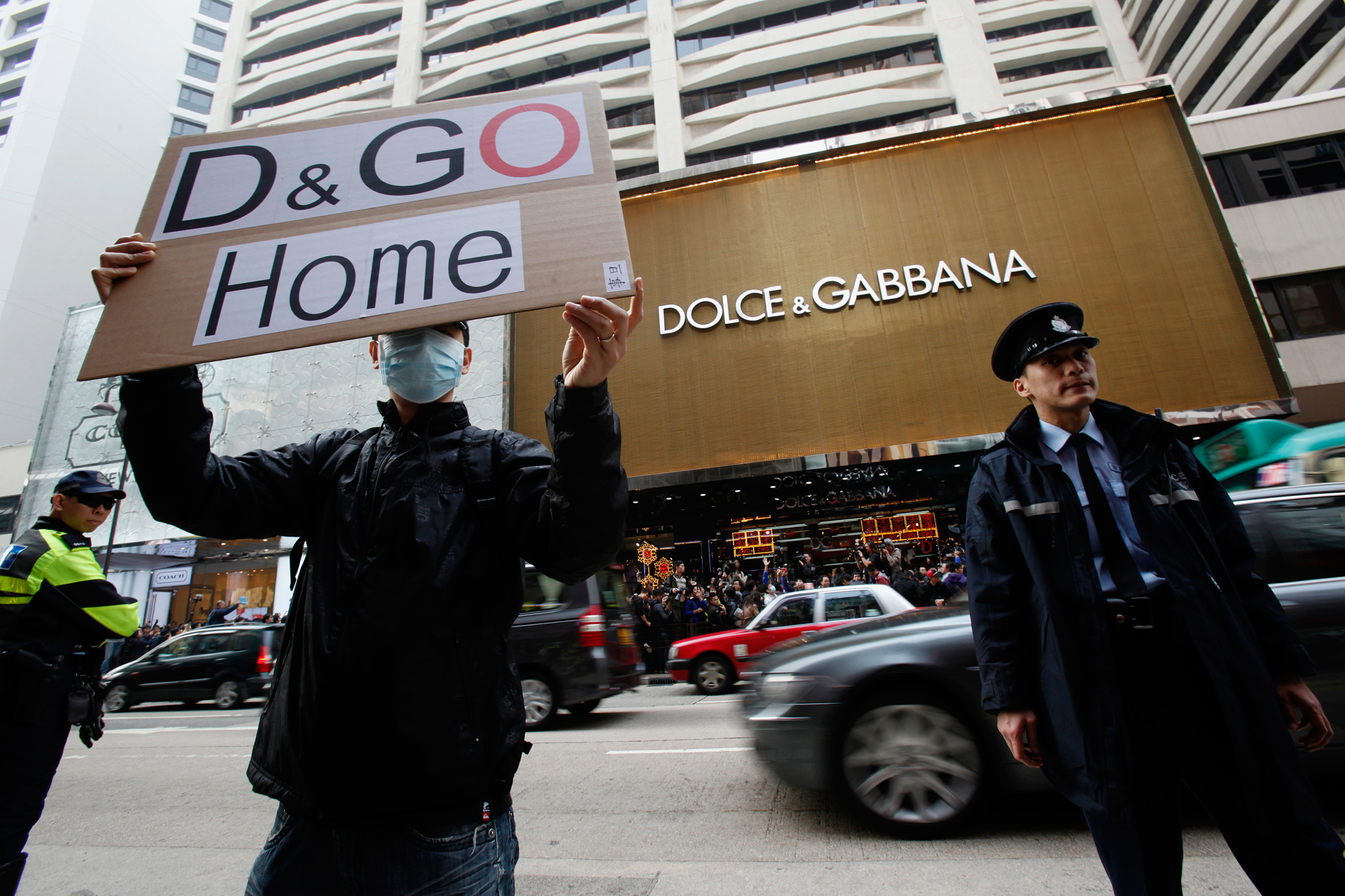 A protester holds a placard outside the flagship store of Dolce & Gabbana in Hong Kong on Jan. 8, 2012. Demonstrations erupted after the fashion chain banned Hongkongers from taking photographs outside its store — to protect its designs, the label said — but appeared to allow mainland Chinese shoppers to snap away without interference. Though seemingly trivial, the photo ban touched a painfully raw nerve among local people, who feared that the territory was being invaded, politically and economically, by Beijing.