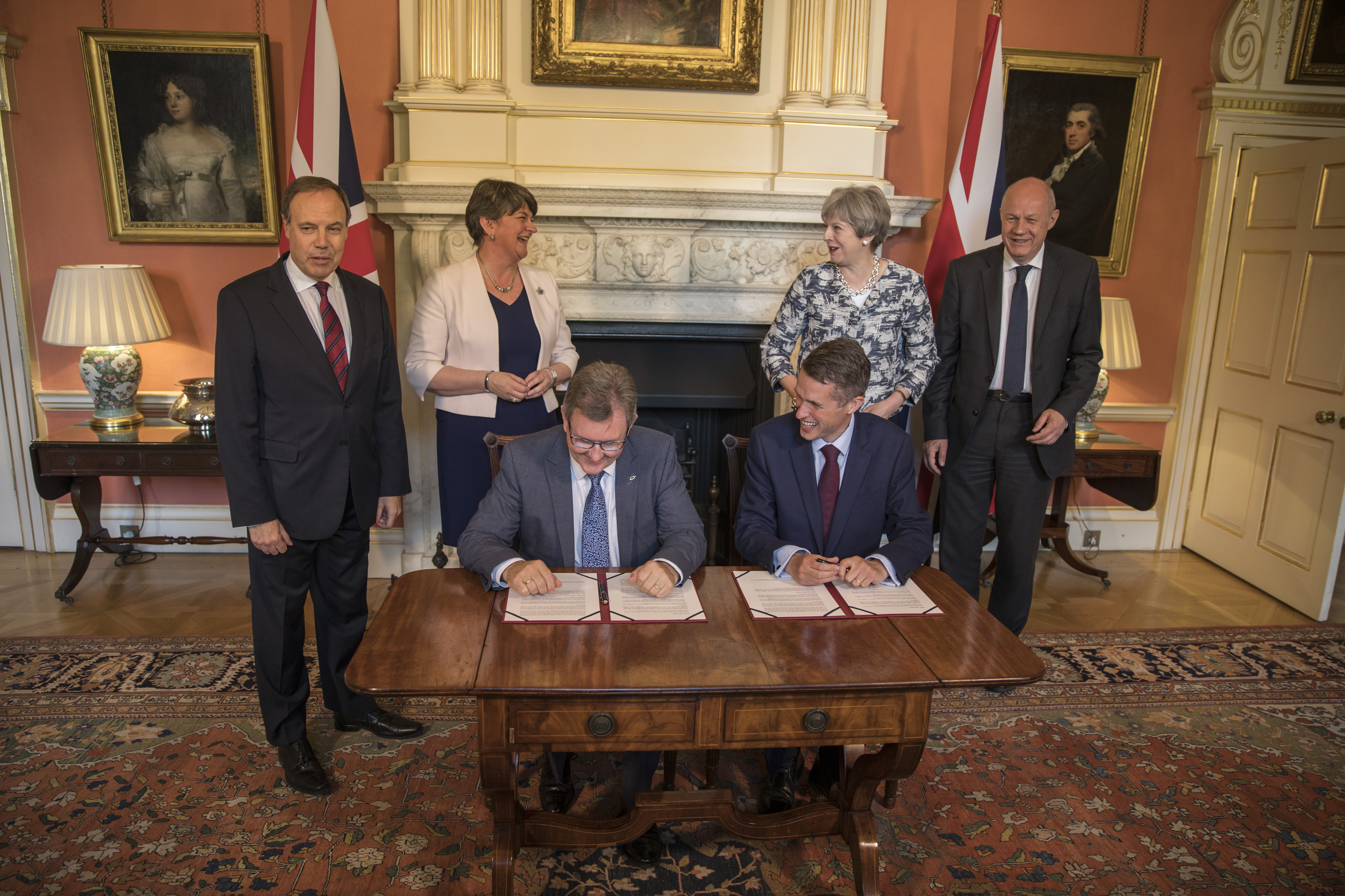 Prime Minister Theresa May (2R) stands with First Secretary of State Damian Green (R), Democratic Unionist Party (DUP) leader Arlene Foster (2L), DUP Deputy Leader Nigel Dodds (L) while DUP MP Jeffrey Donaldson (3L) and Parliamentary Secretary to the Treasury, and Chief Whip, Gavin Williamson sit and sign paperwork inside 10 Downing Street on June 26, 2017 in London, England.