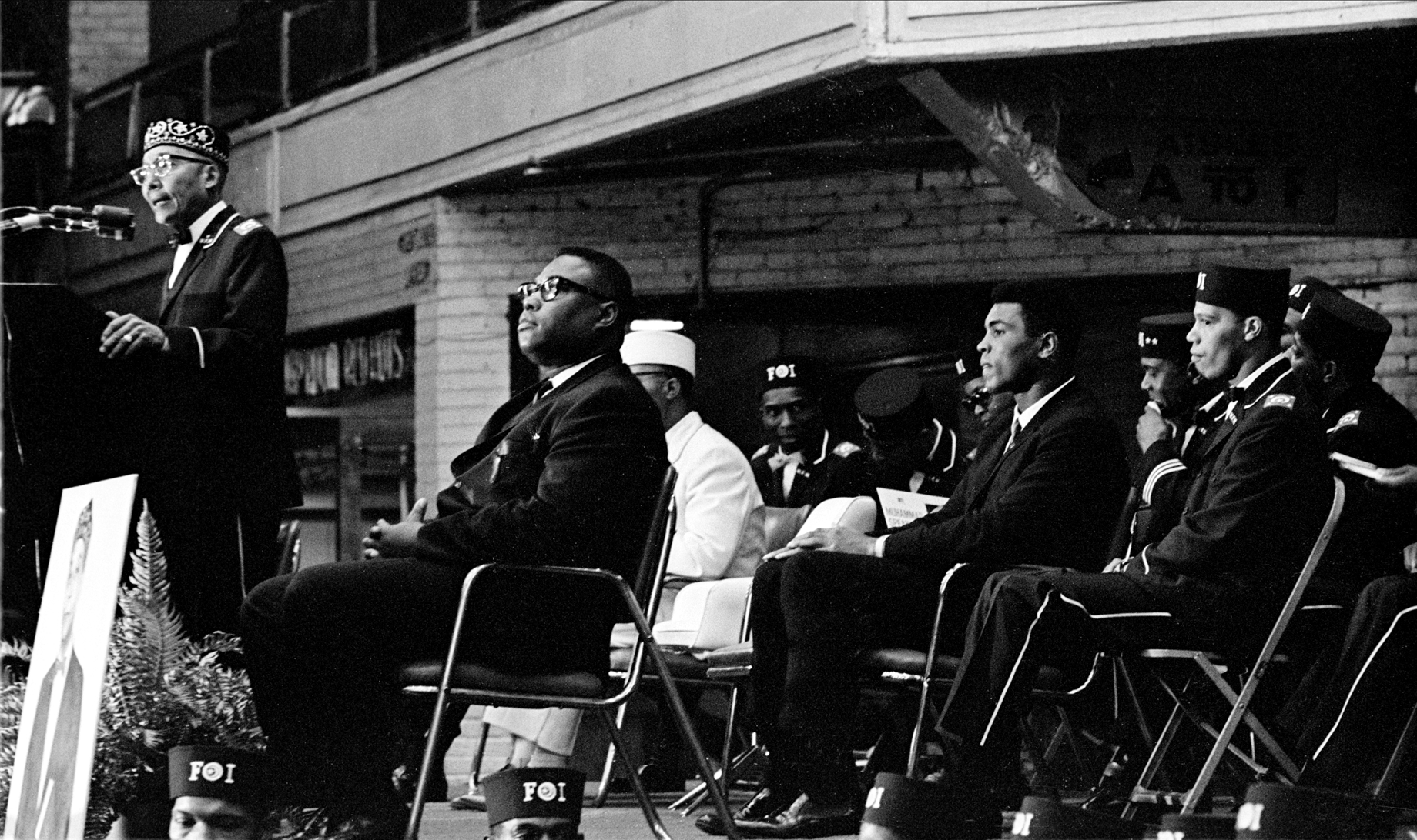 Elijah Muhammad speaks during Saviour's Day celebrations, while Muhammad Ali listens (center, fore), at the International Ampitheatre, Chicago, IL, on Feb. 27, 1966.