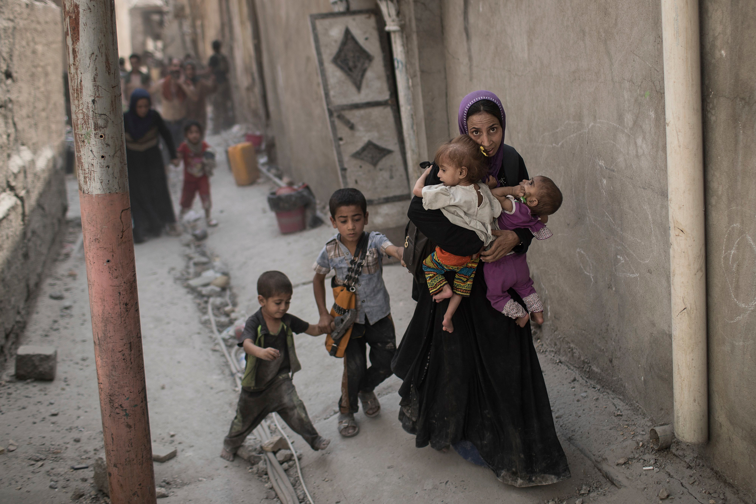 Iraqi civilians flee through an alley as Iraqi Special Forces continue their advance against Islamic State militants in the Old City of Mosul, Iraq, on July 3, 2017.