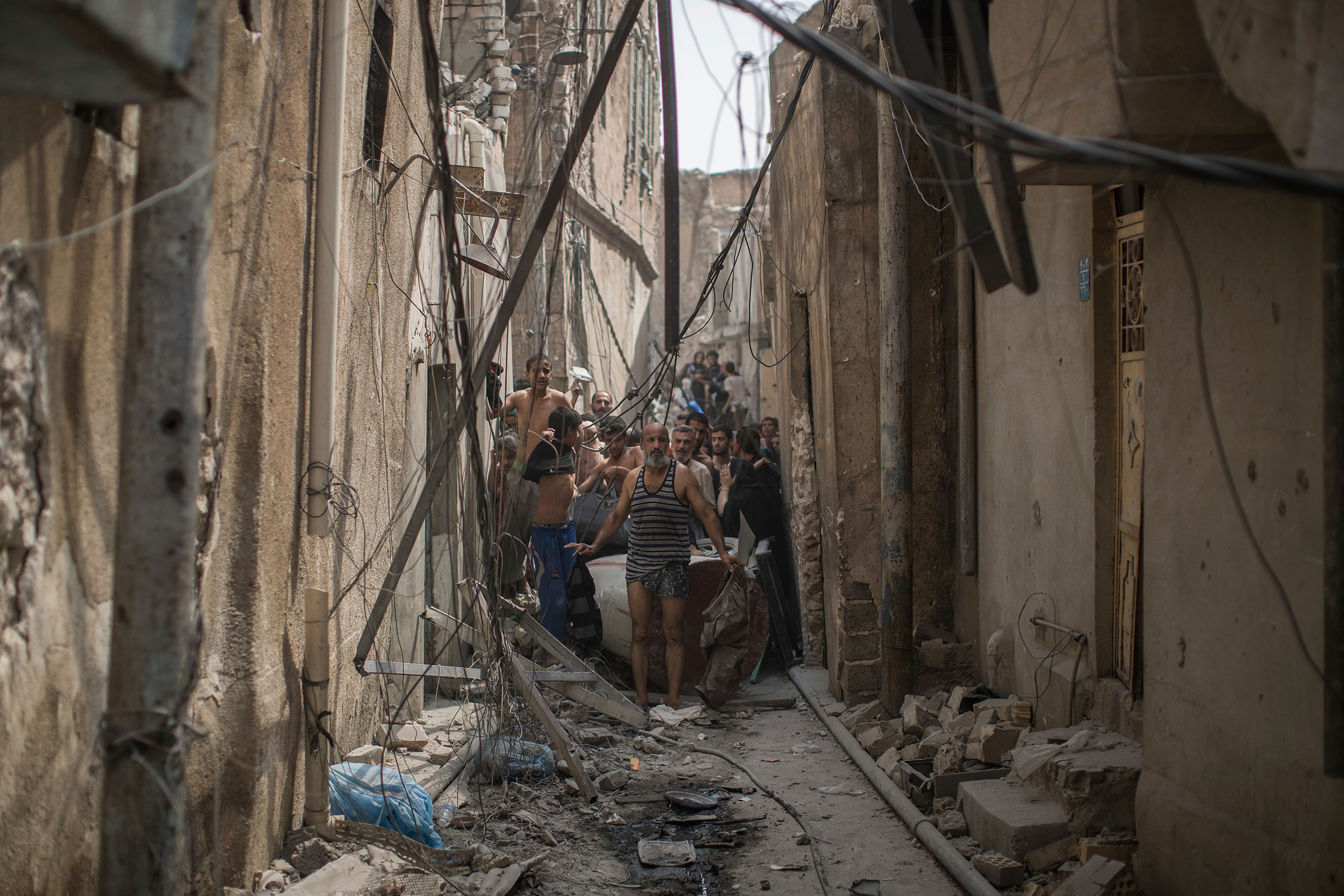 Civilians trying to flee get undressed to be checked for explosives after suicide bombers exploded as Iraqi forces continue their advance against Islamic State militants in the Old City of Mosul, Iraq, on July 3, 2017.