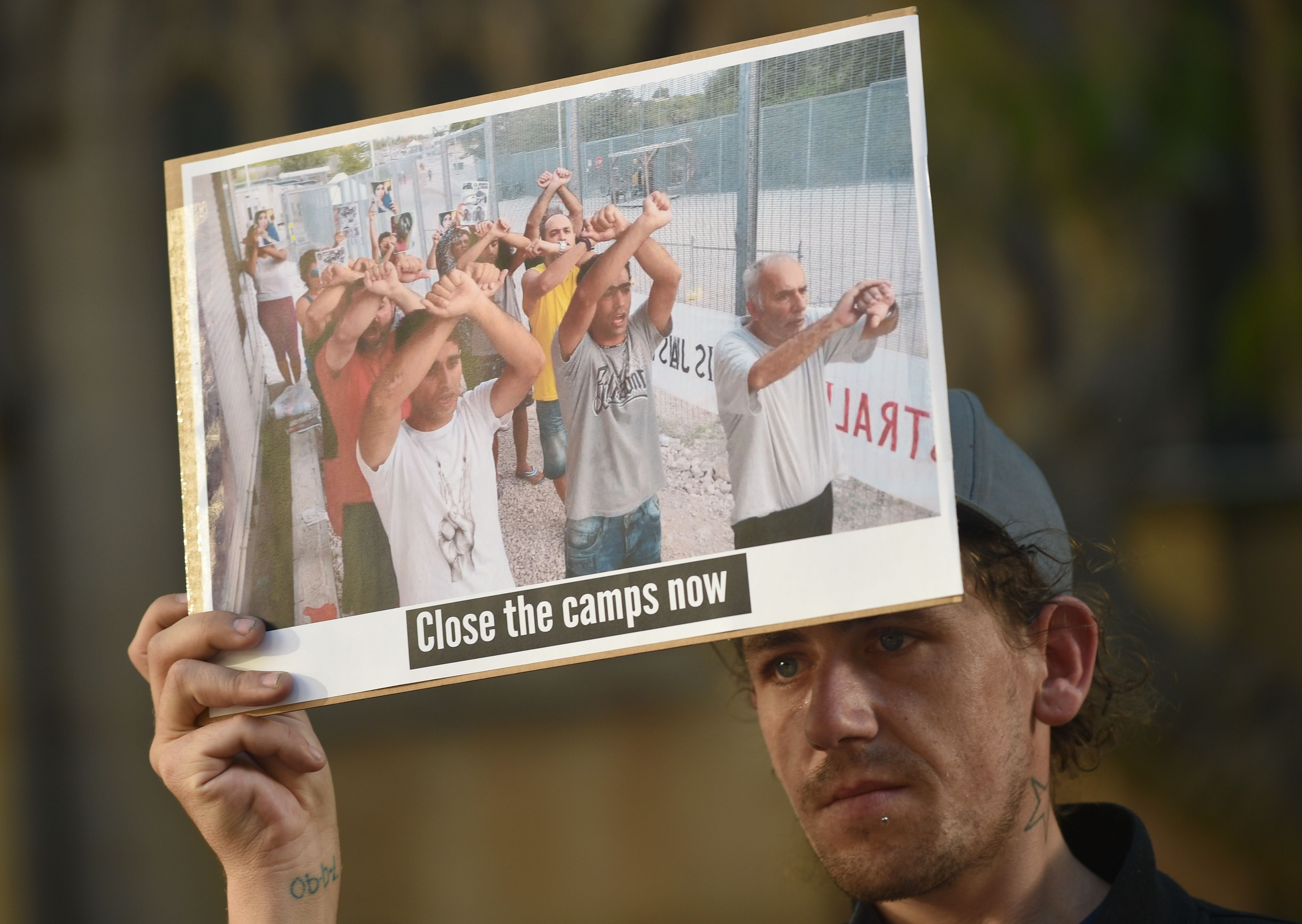 A refugee supporter holds a placard as he and others protest in Sydney on Oct. 5, 2016.
